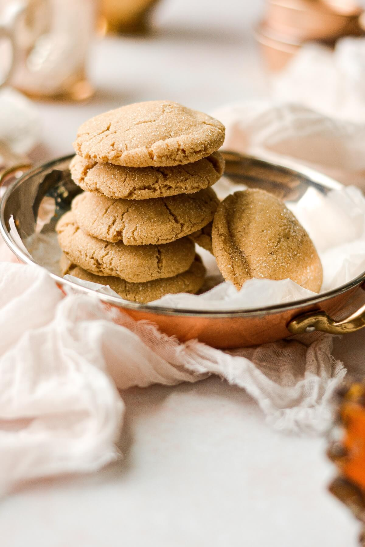 A stack of soft maple cookies on a silver and copper tray.