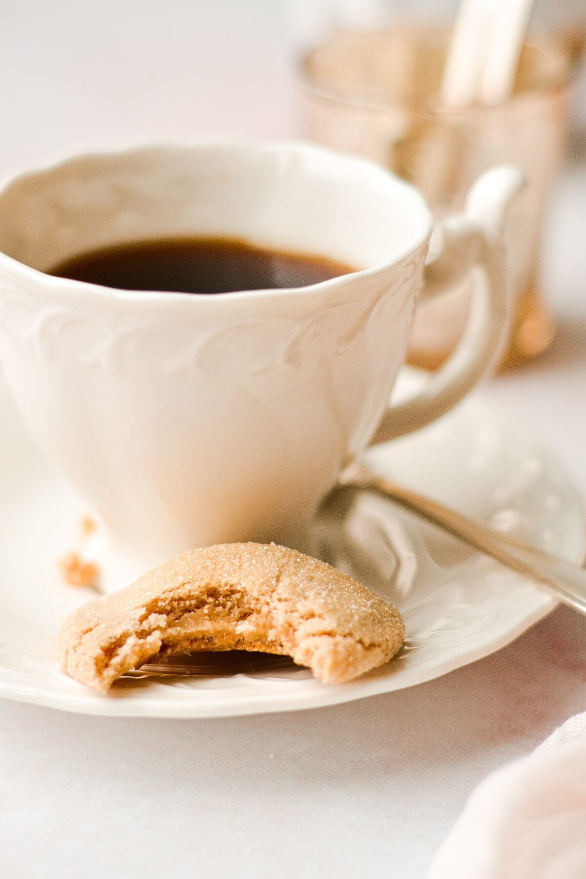 A half eaten maple cookie next to a cup of coffee.
