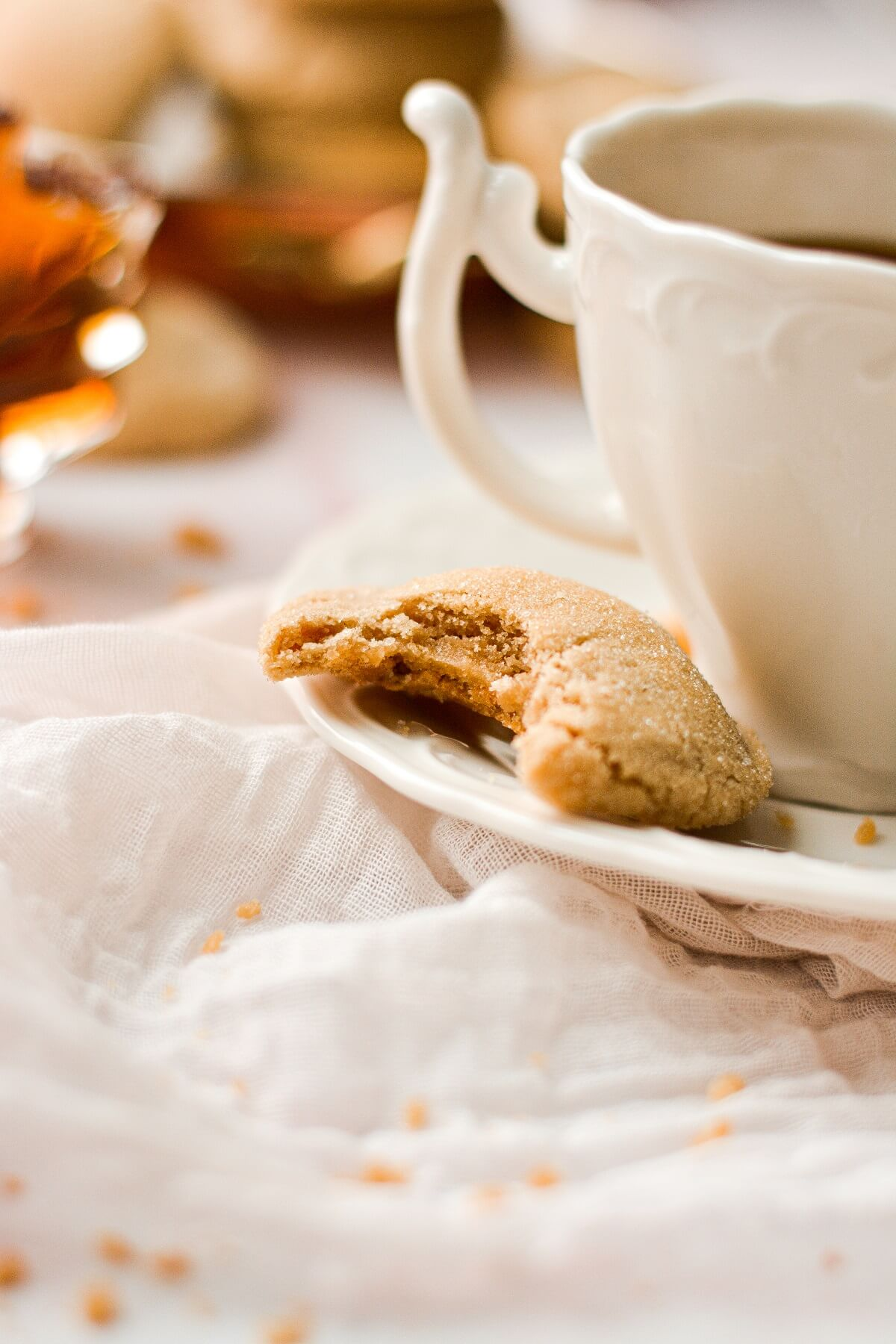 A half eaten soft maple cookie next to a cup of coffee.
