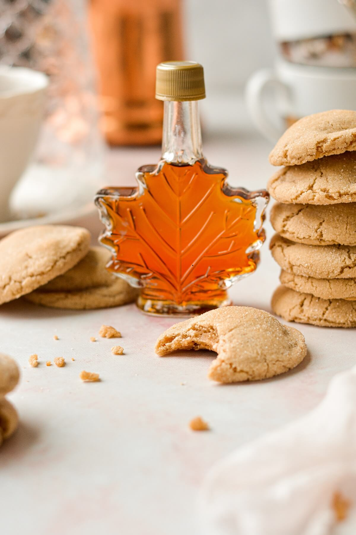 Soft maple cookies next to a maple leaf shaped glass syrup bottle.