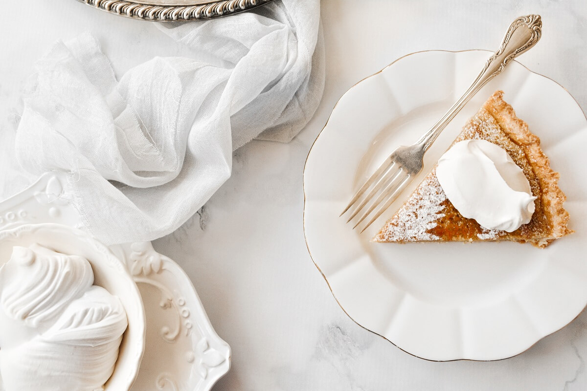 A slice of maple tart, topped with whipped cream.