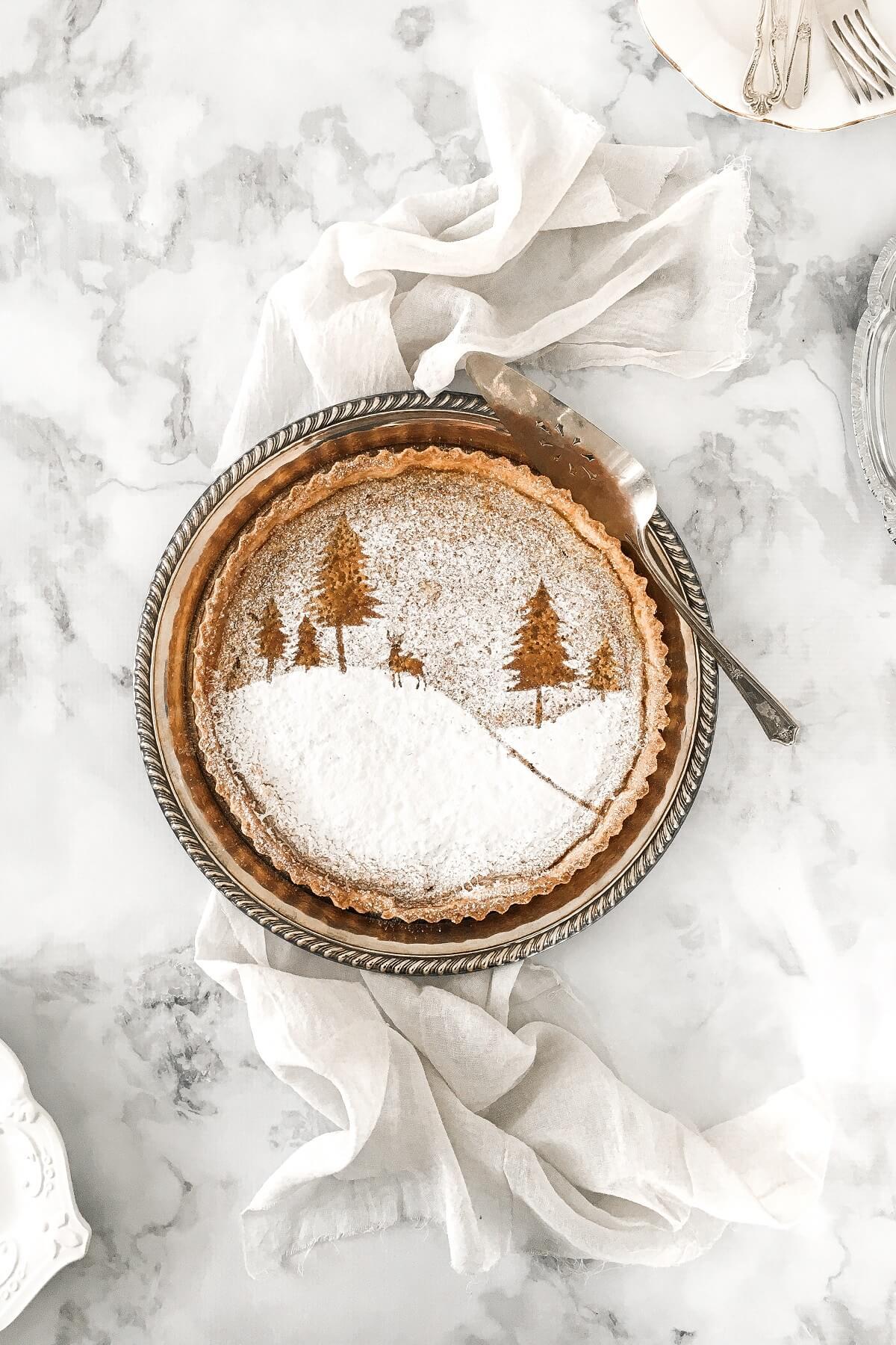Maple tart with a powdered sugar stencil of a snowy winter scene.