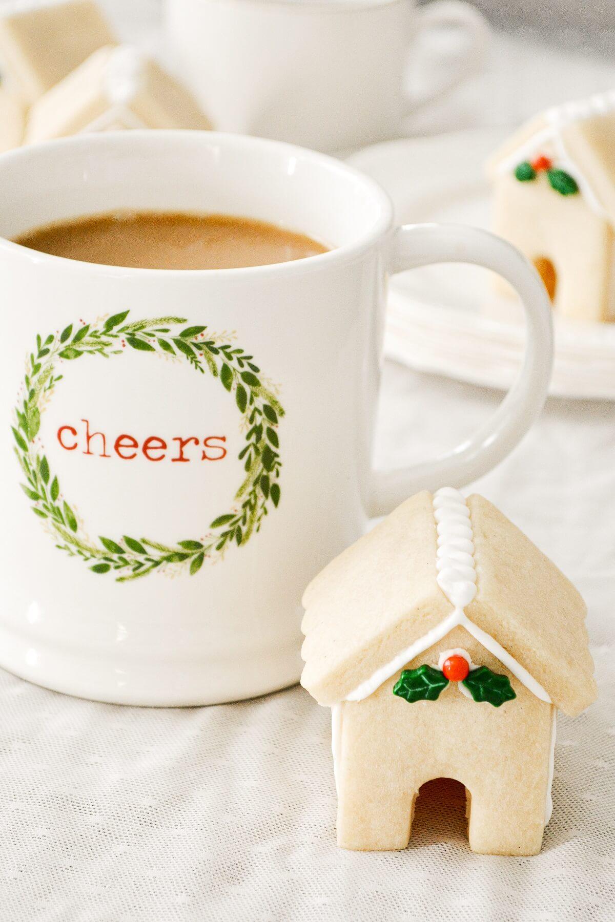 A mini vanilla bean shortbread cookie house, with a Christmas mug full of coffee.