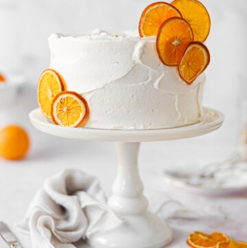 An orange cake, garnished with dried orange slices, on a white cake stand.