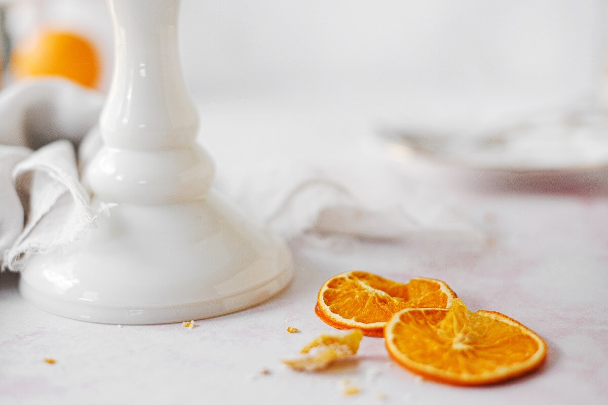 Closeup of dried orange slices next to a white cake stand.