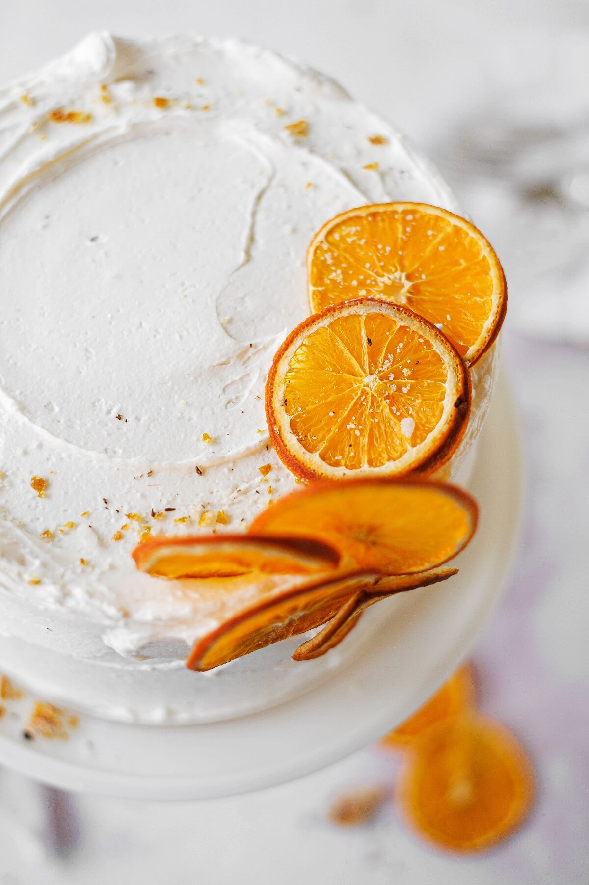 An orange cake, topped with dried orange slices and candied orange peel.