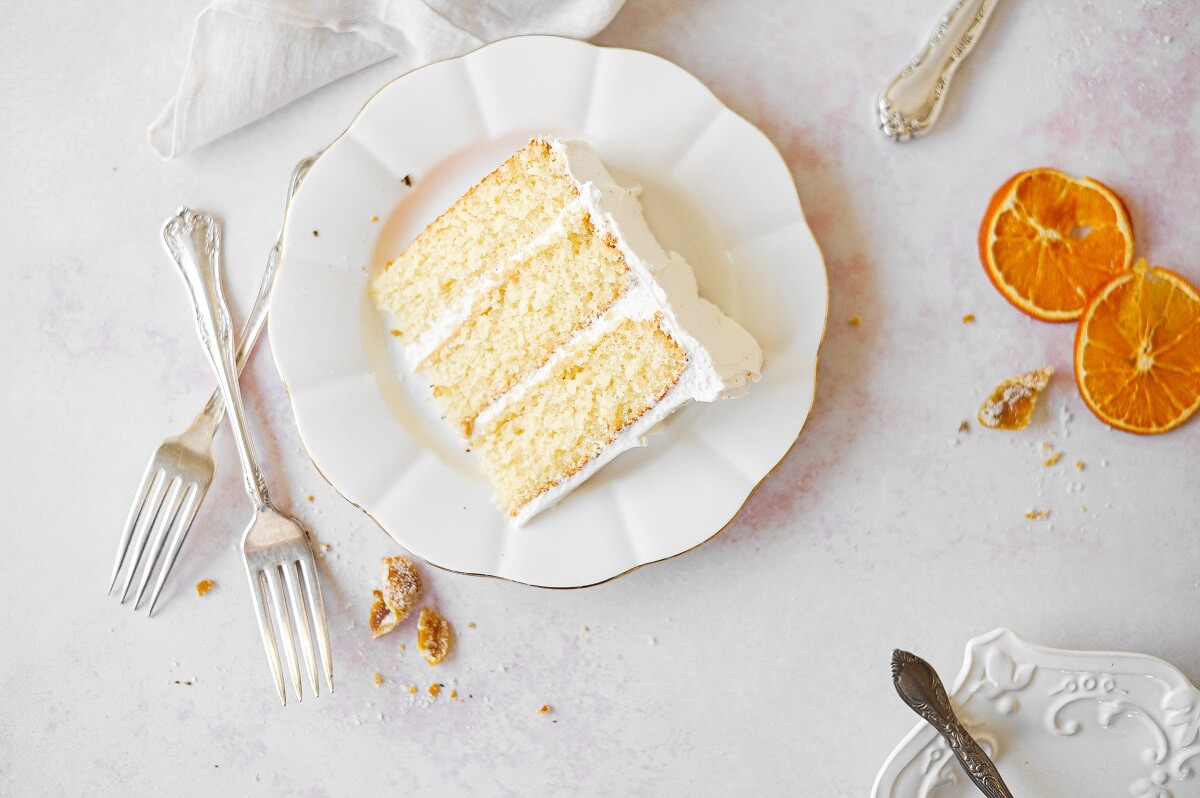 A slice of orange layer cake on a white plate, with dried orange slices scattered around.