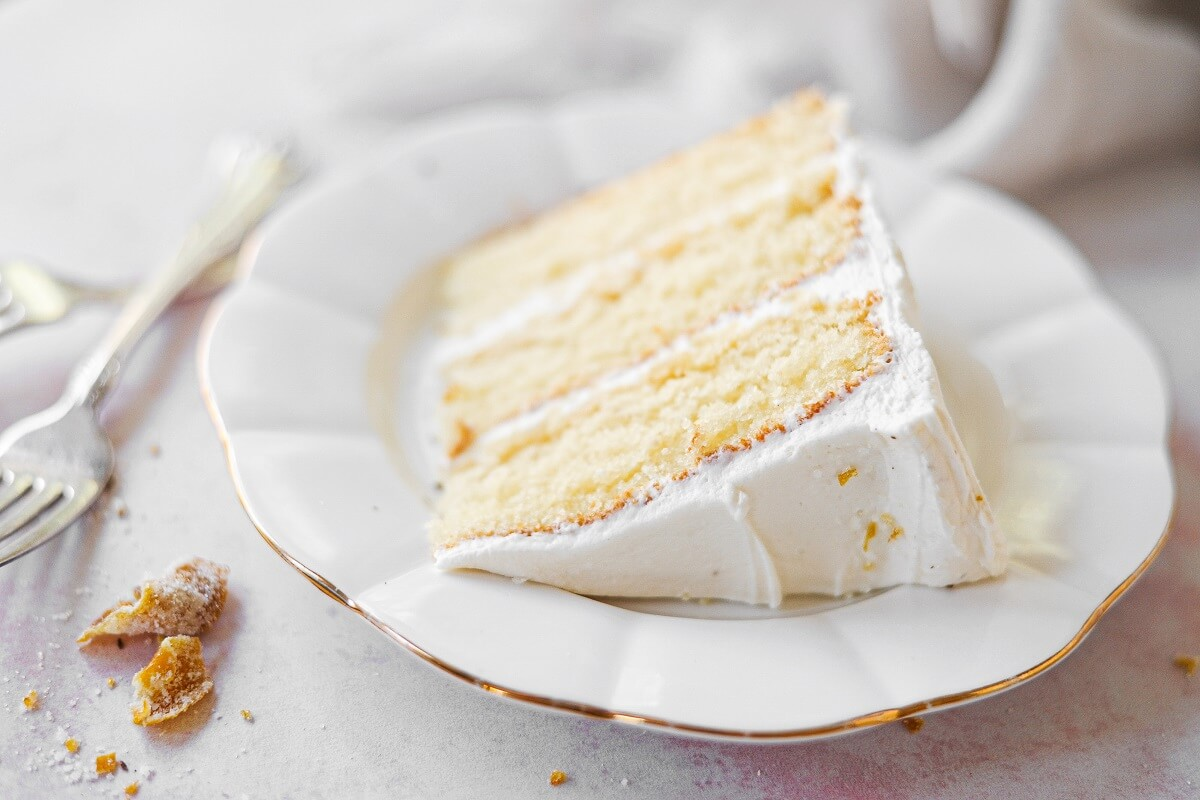 A slice of orange layer cake on a white plate.