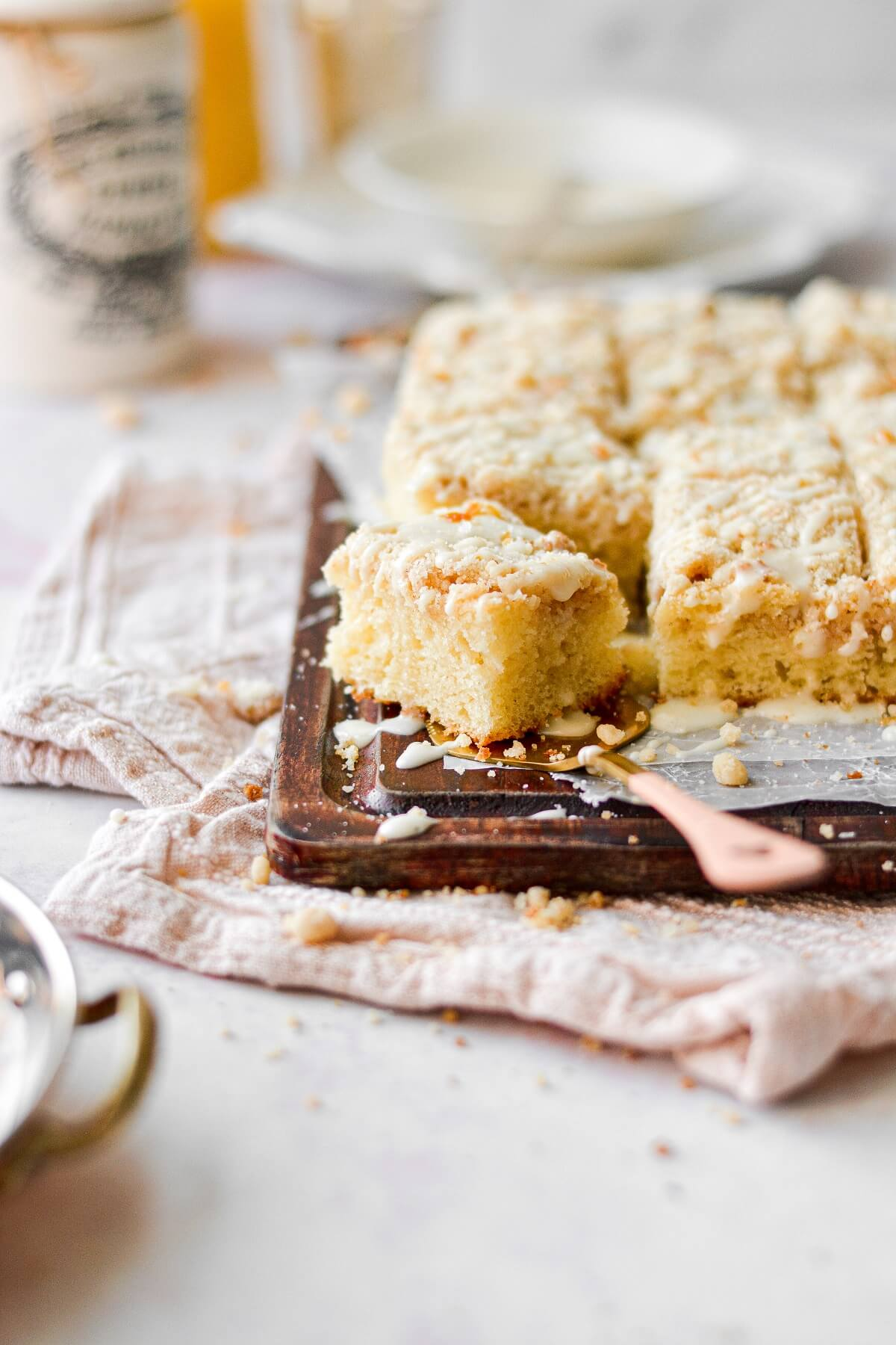 Orange sour cream coffee cake, on a cutting board with a pink and gold cake server.
