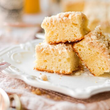 Three pieces of orange sour cream coffee cake, stacked on a white plate with a pink linen napkin.