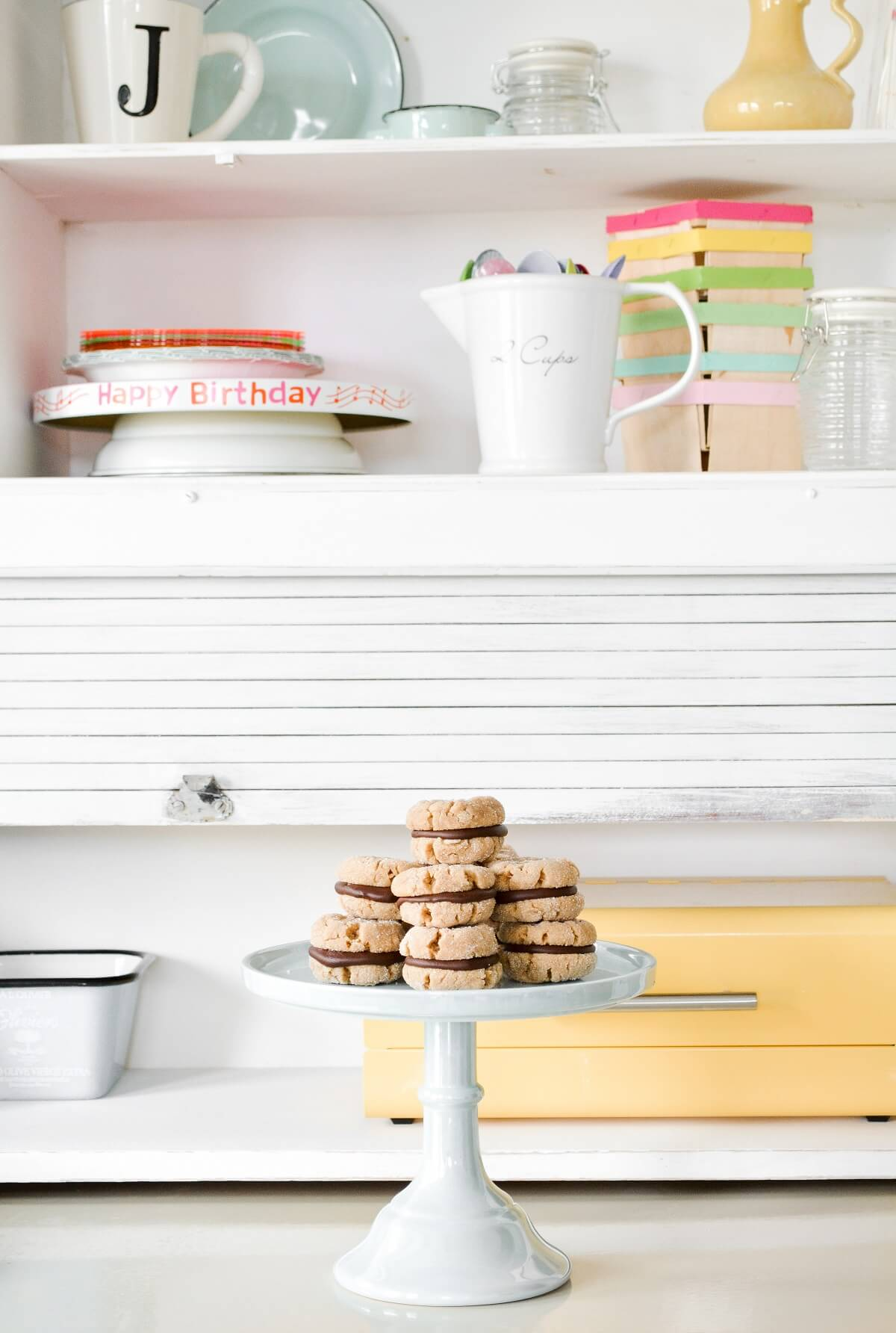 Peanut butter cookie sandwiches, filled with chocolate ganache, stacked on a light blue cake stand.