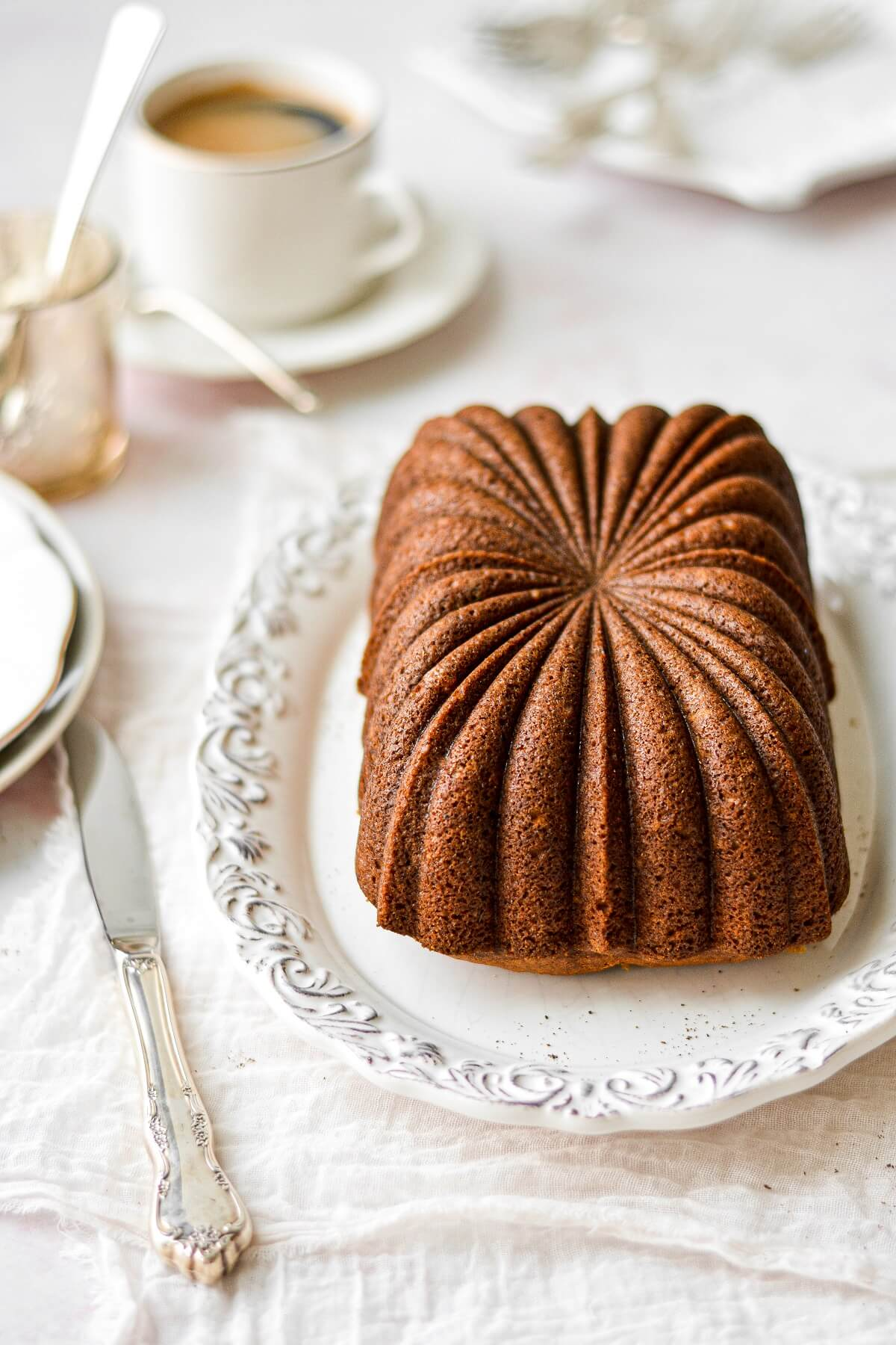 A loaf of pumpkin bread on a white plate.