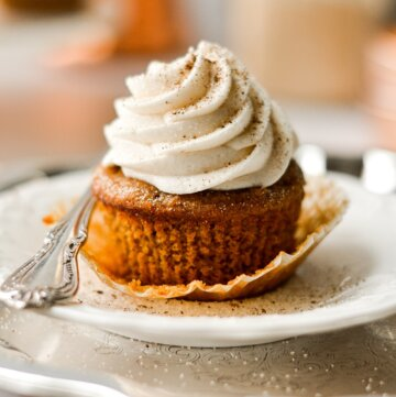 A pumpkin cupcake, with the wrapper unwrapped, on a white plate.