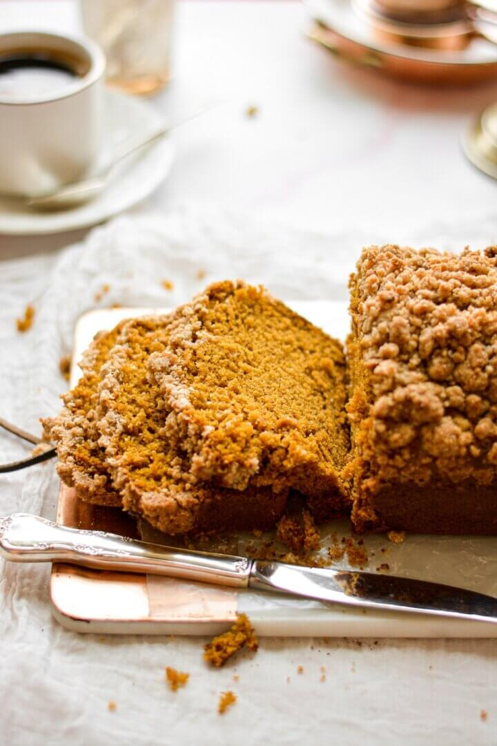 A loaf of pumpkin streusel bread, with a few pieces sliced on a cutting board.