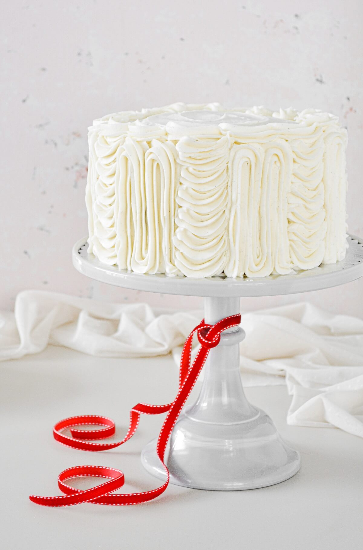 Red velvet cake on a light gray cake stand, with a red ribbon tied around the cake stand.