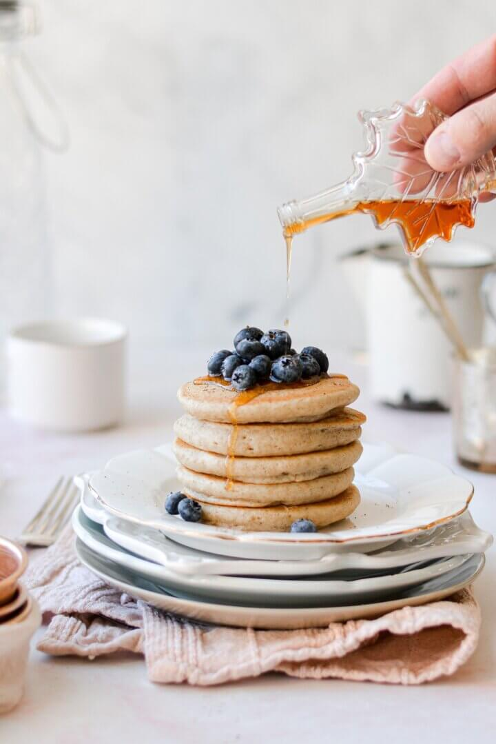 A stack of pancakes topped with blueberries, with maple syrup being drizzled on top.