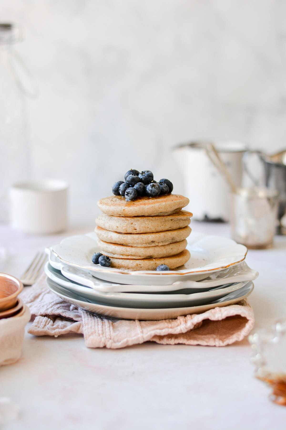 A stack of pancakes topped with blueberries.