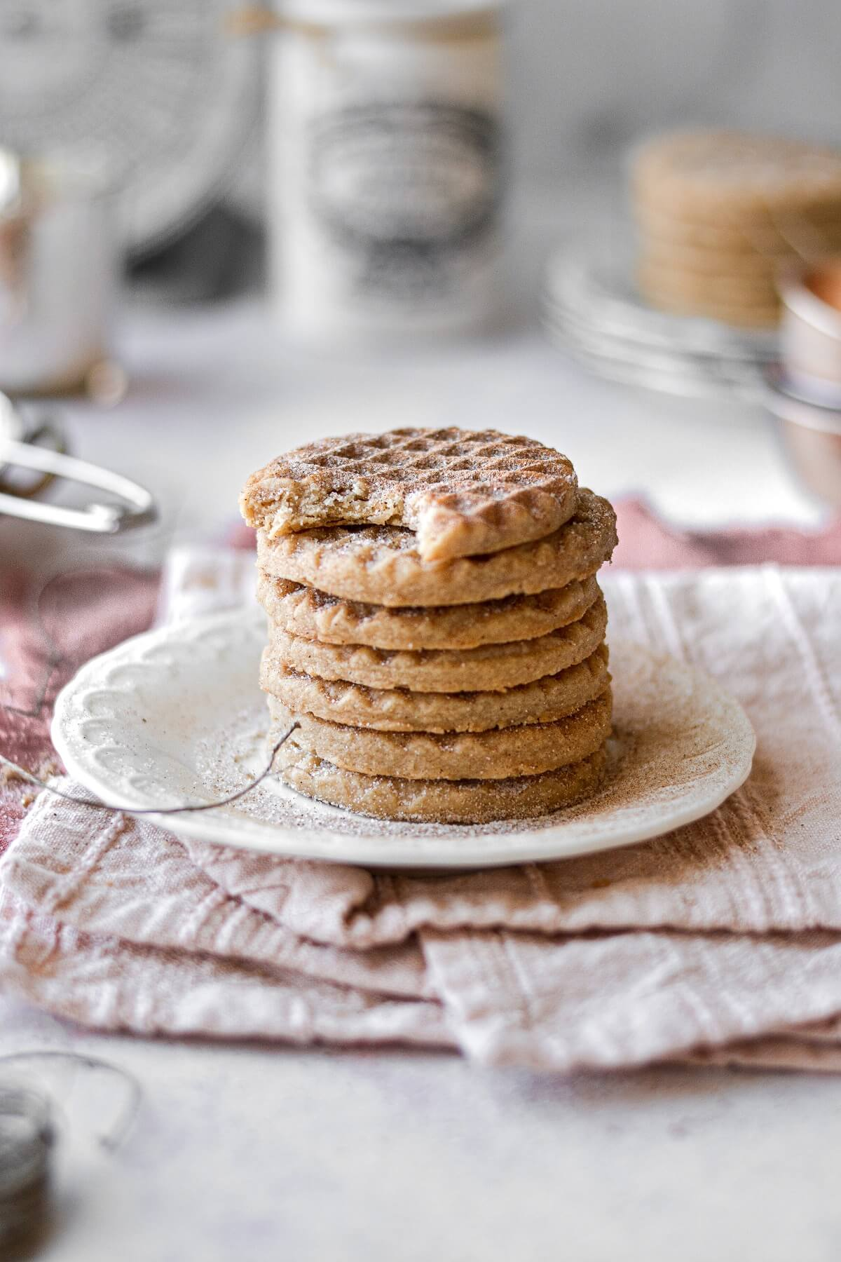 A stack of snickerdoodle shortbread cookies, the top one with a bite taken.
