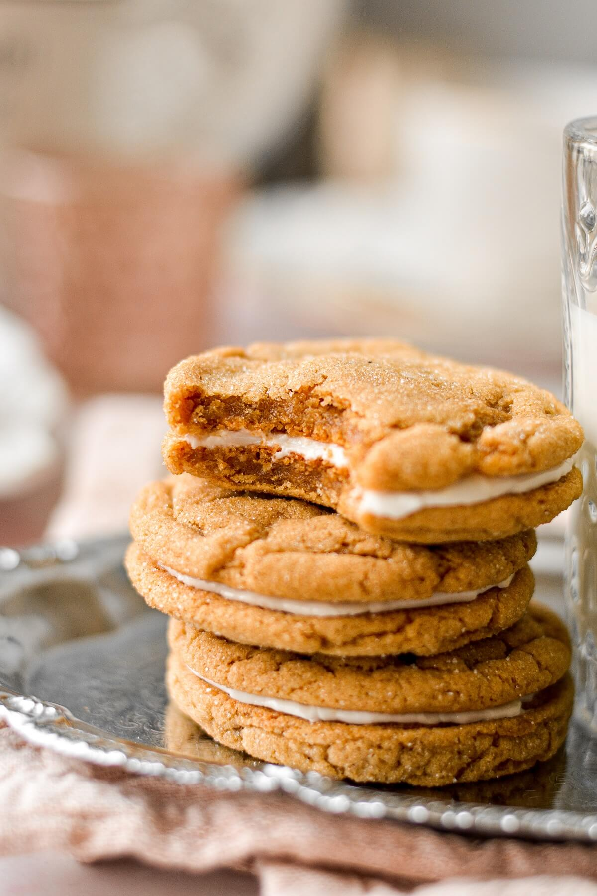 Soft ginger molasses cookies, one with a bite taken.