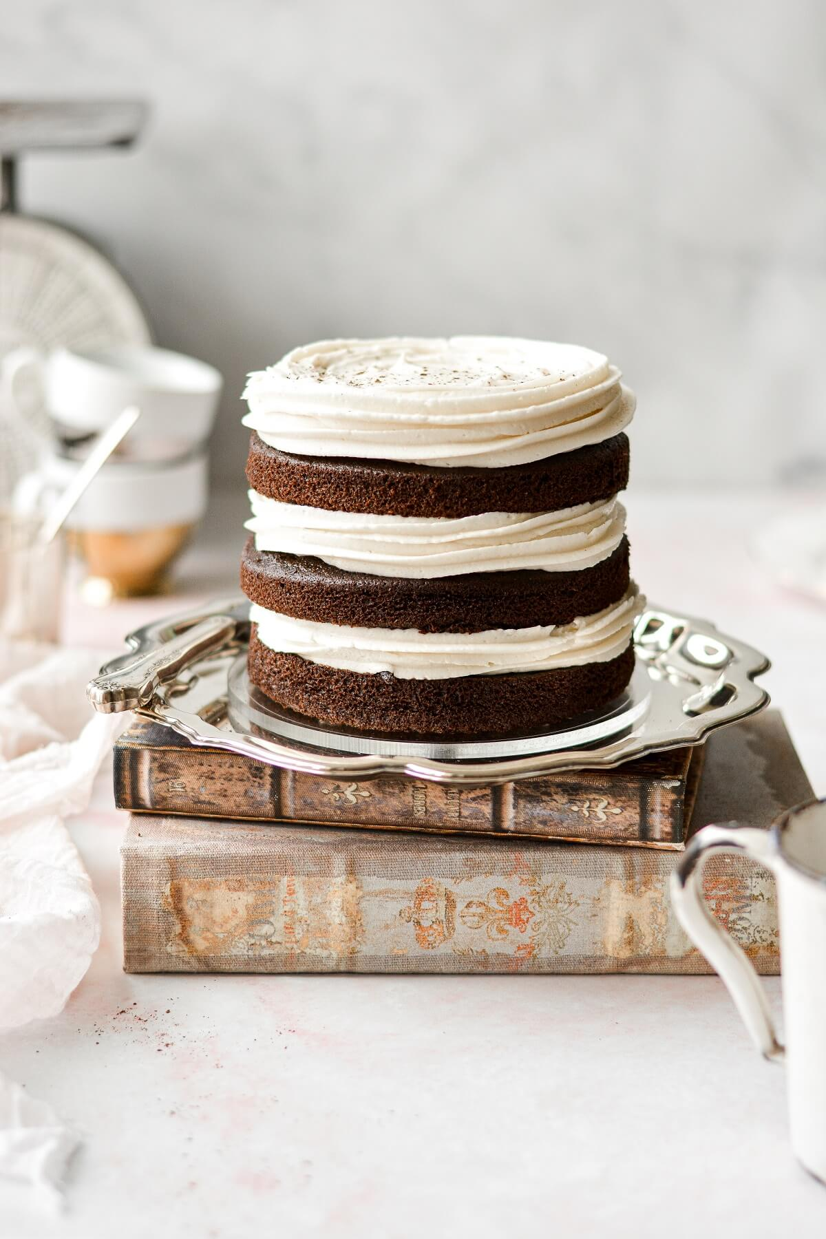 Three naked layers of spice cake, with swirls of cream cheese buttercream.