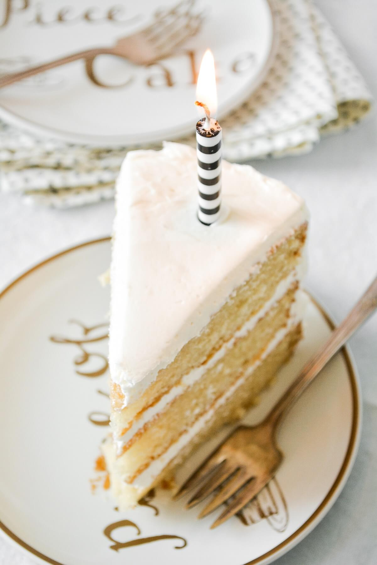 A slice of vanilla cake with a black and white striped candle.