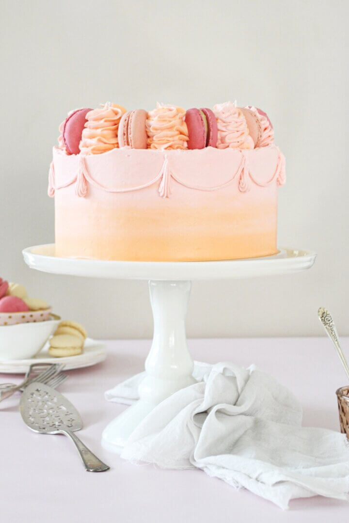 A cake on a white cake stand, frosted with pink and orange watercolor buttercream, topped with macarons and swirls of buttercream.