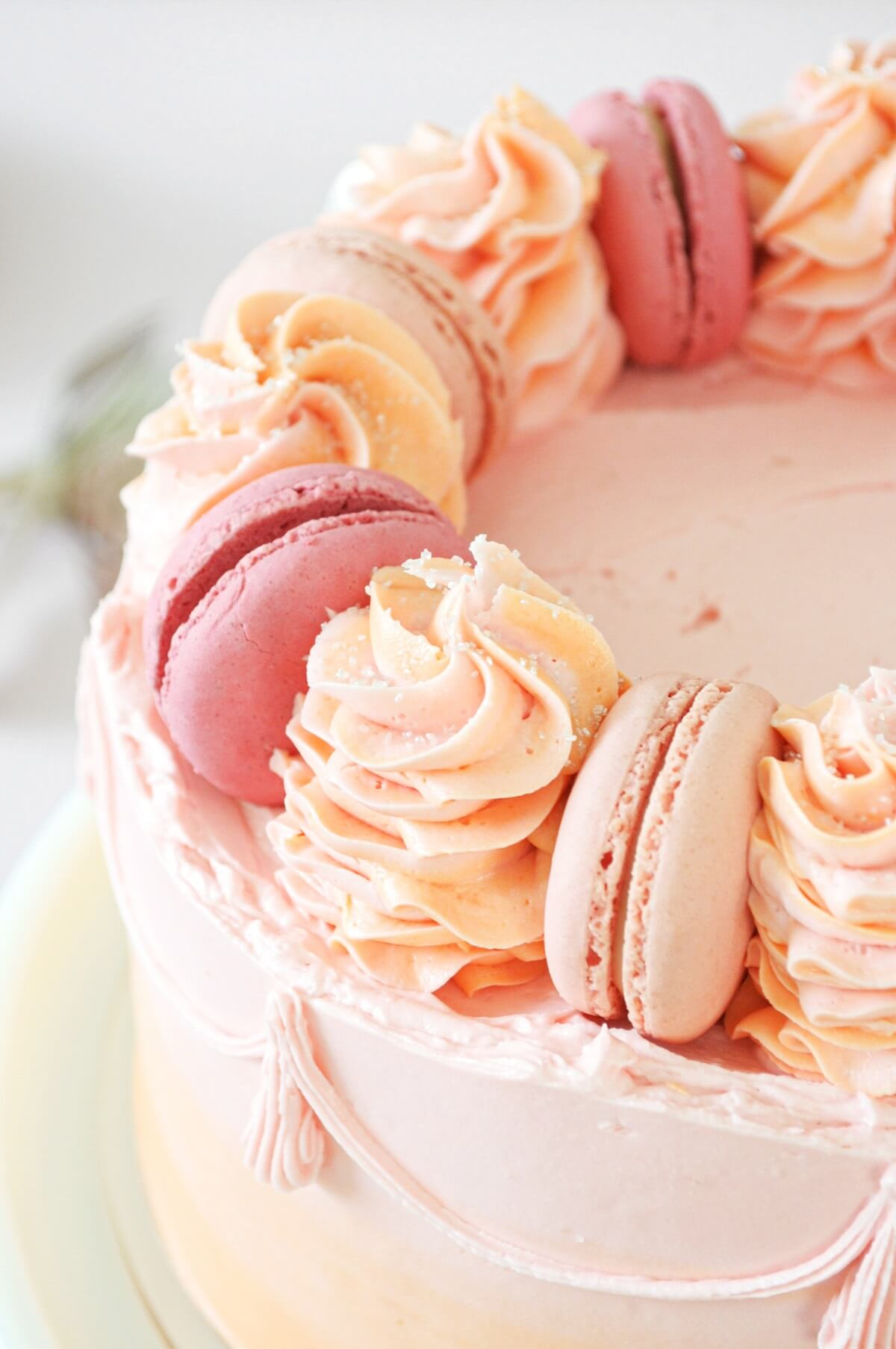Closeup of pink macarons and swirls of buttercream on a cake frosted with pink and orange watercolor buttercream.