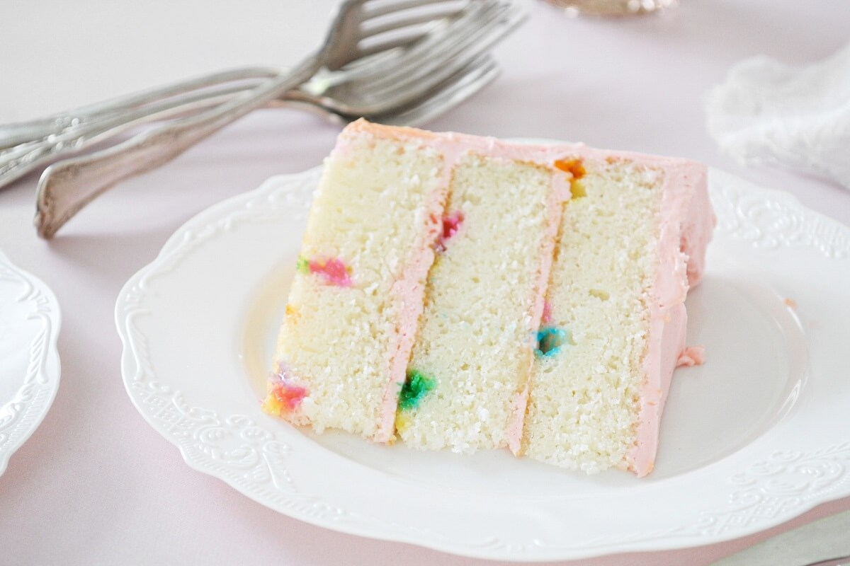 A slice of funfetti cake with pink buttercream, on a white plate.