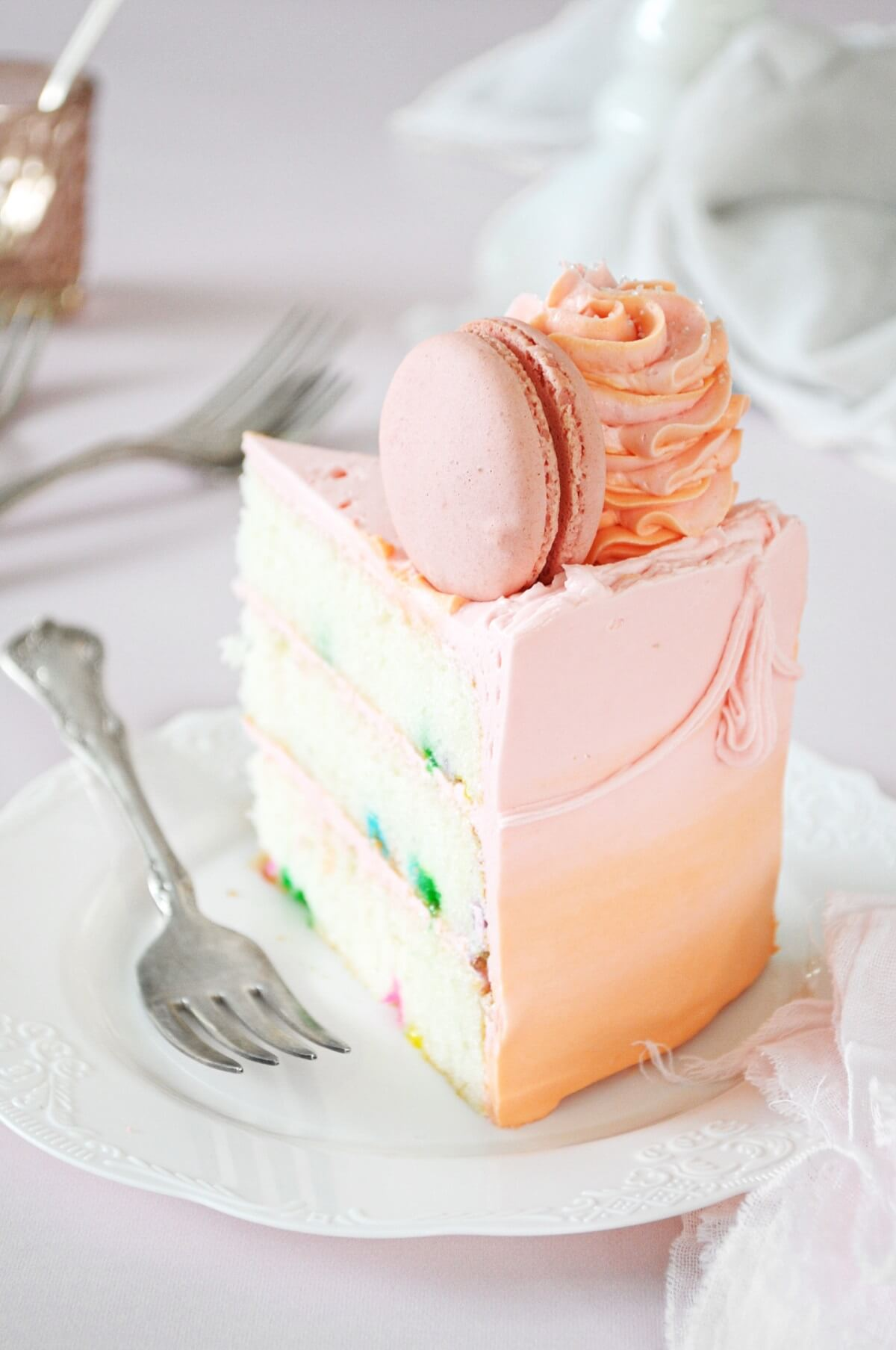 A slice of funfetti cake, frosted with pink and orange watercolor buttercream, topped with a macaron and swirl of buttercream.