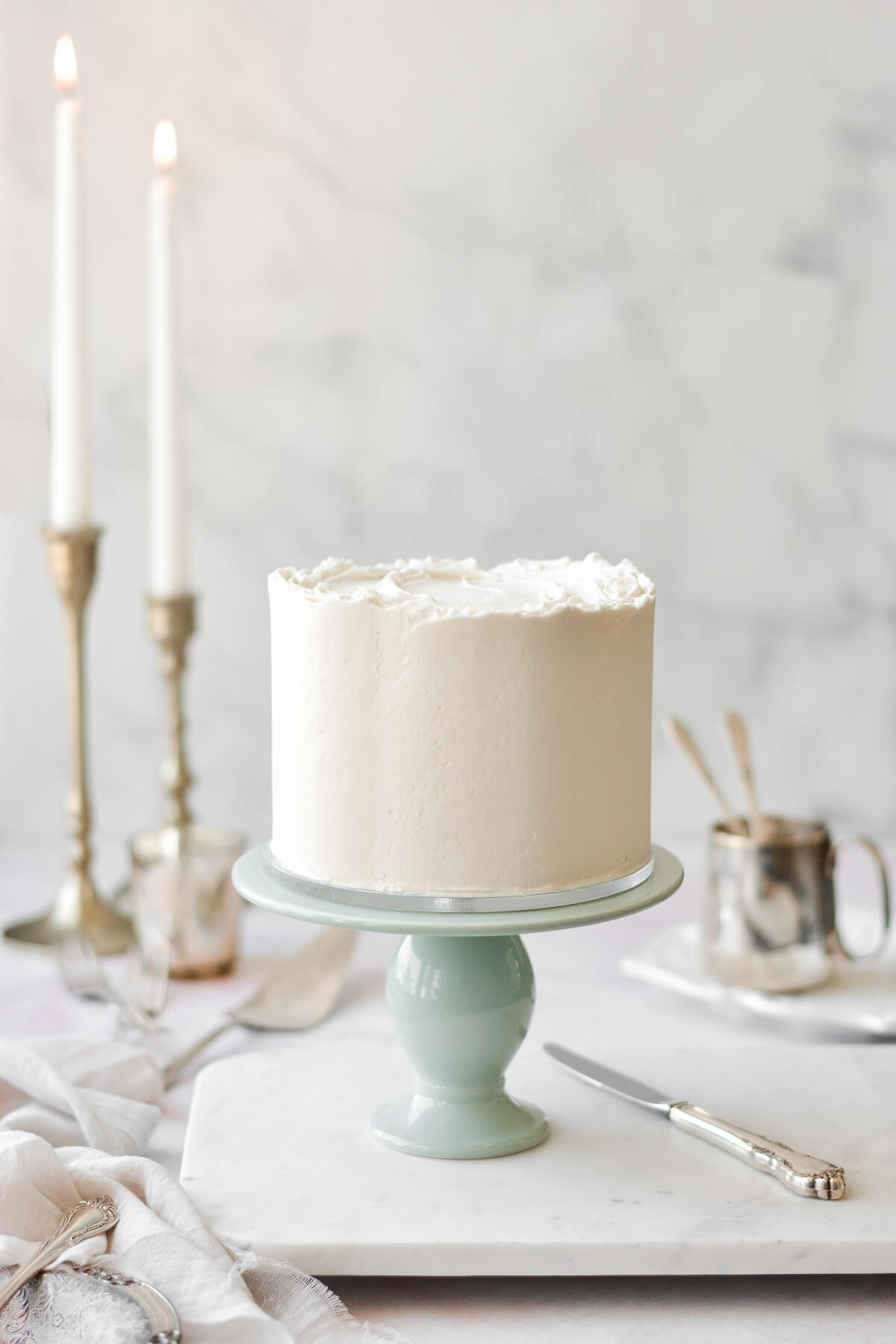 White velvet cake on a sage green cake stand, with taper candles in the background.