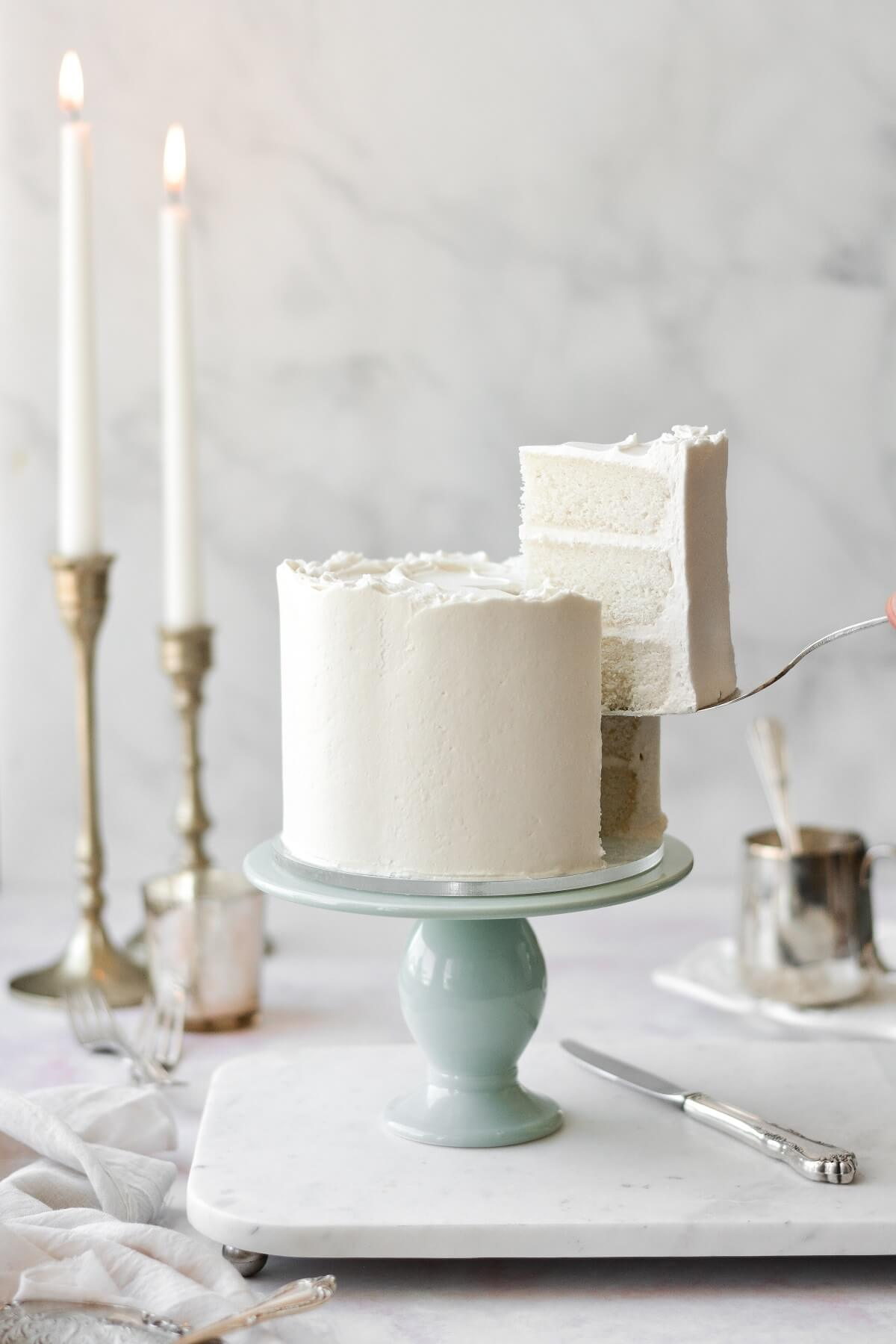 White velvet cake frosted with perfect American buttercream, on a sage green cake stand, with a piece being lifted out by a silver cake server.