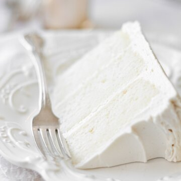 A slice of white velvet cake on a white plate, with a silver fork..