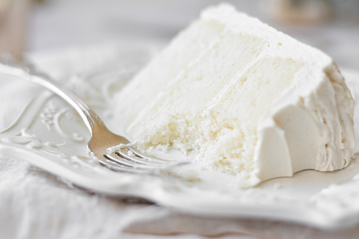 A slice of white velvet cake with a bite taken out of it, on a white plate.