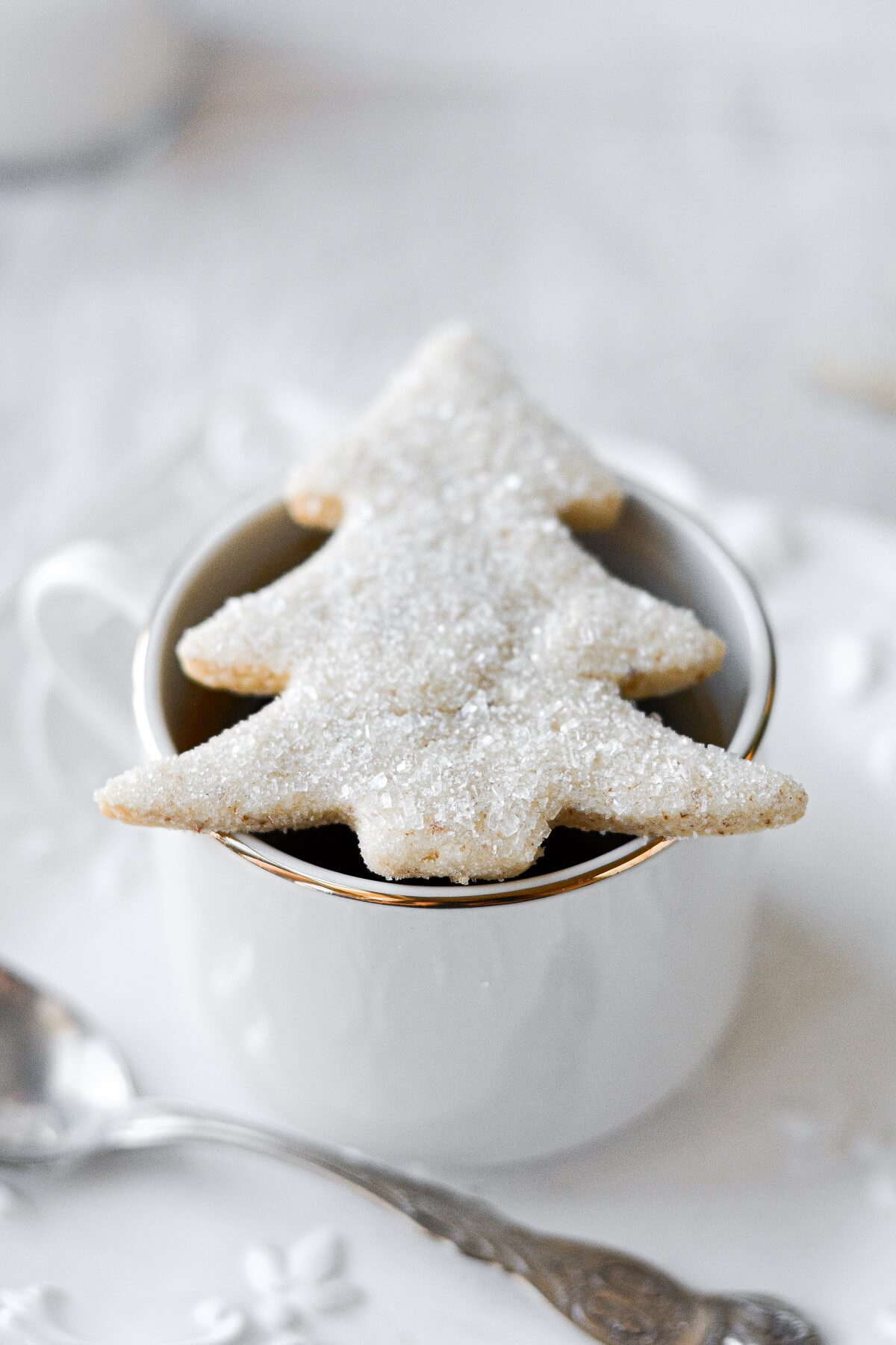 An almond shortbread sugar cookie shaped like a Christmas tree, resting on a cup of coffee.