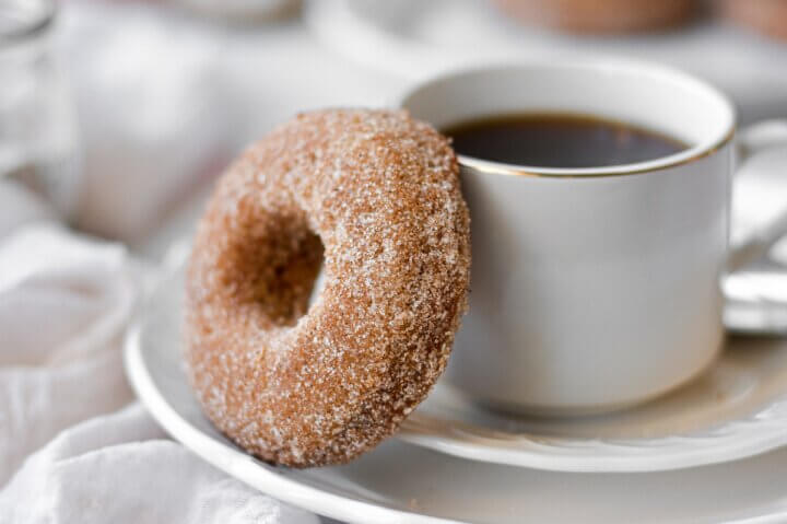 An apple cider doughnut next to a cup of coffee.