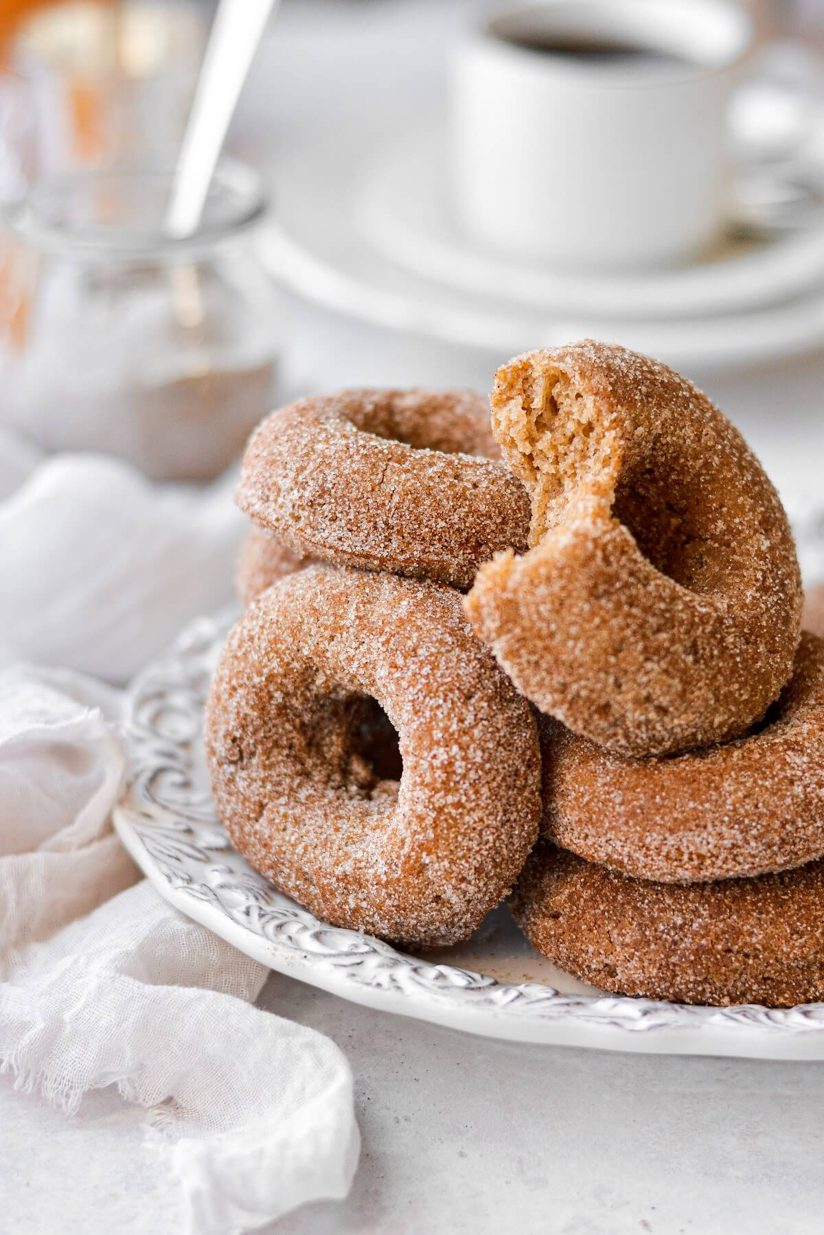 Apple cider doughnuts, one with a bite taken.