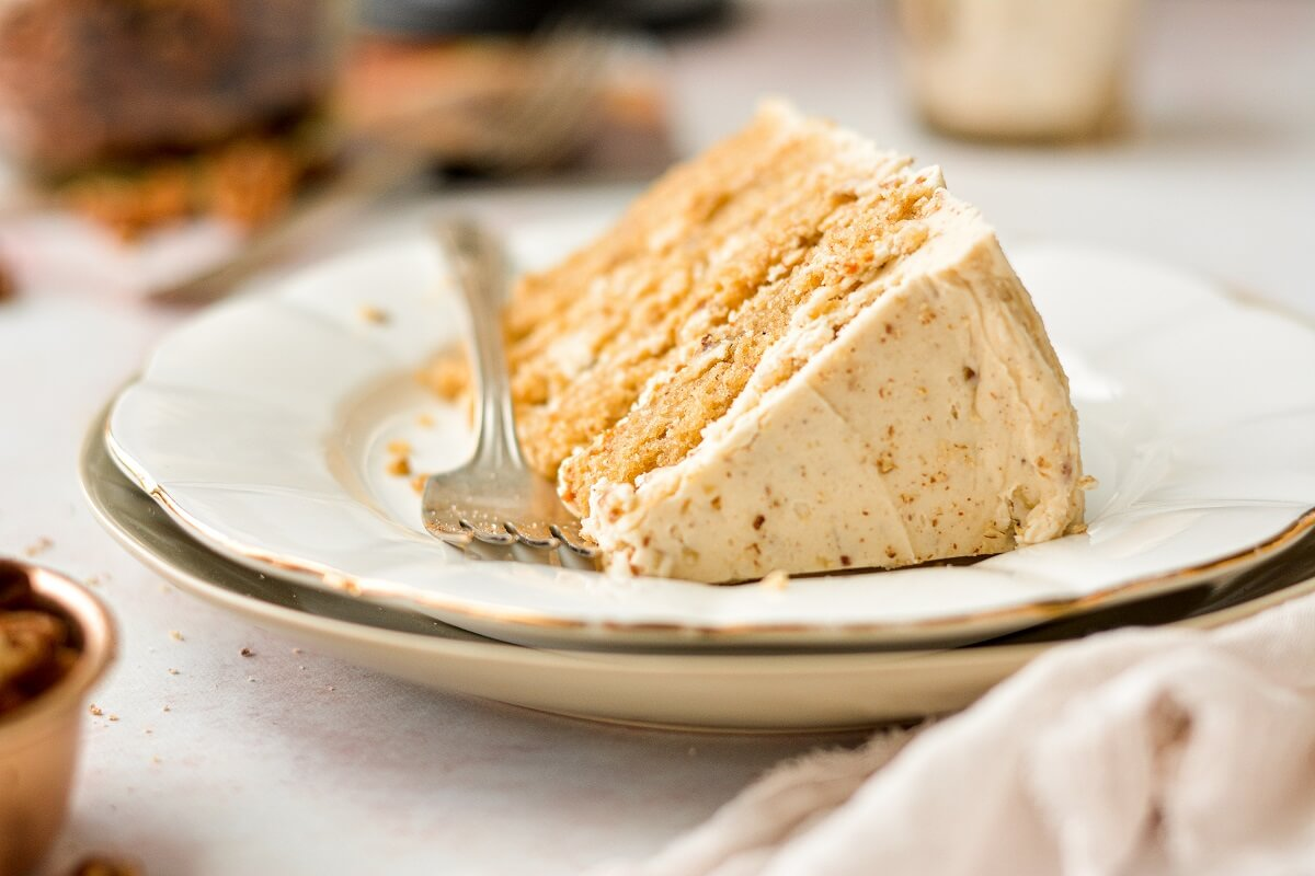 A slice of butter pecan cake on a white plate.