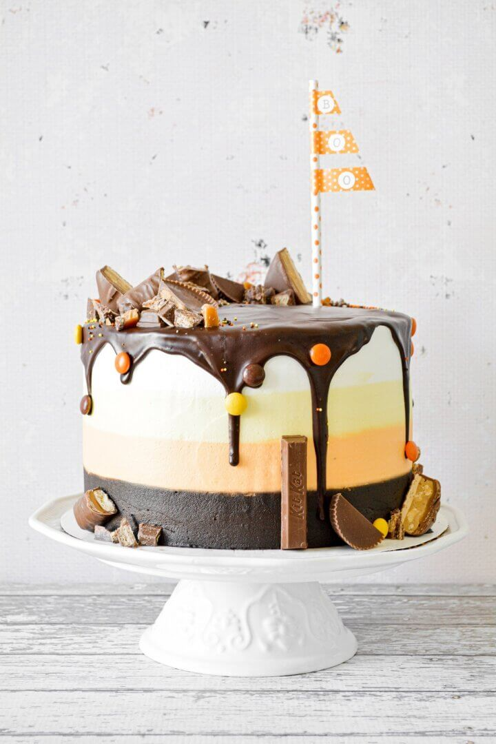 Halloween cake with striped layers of cake and buttercream in candy corn colors, decorated with candy.