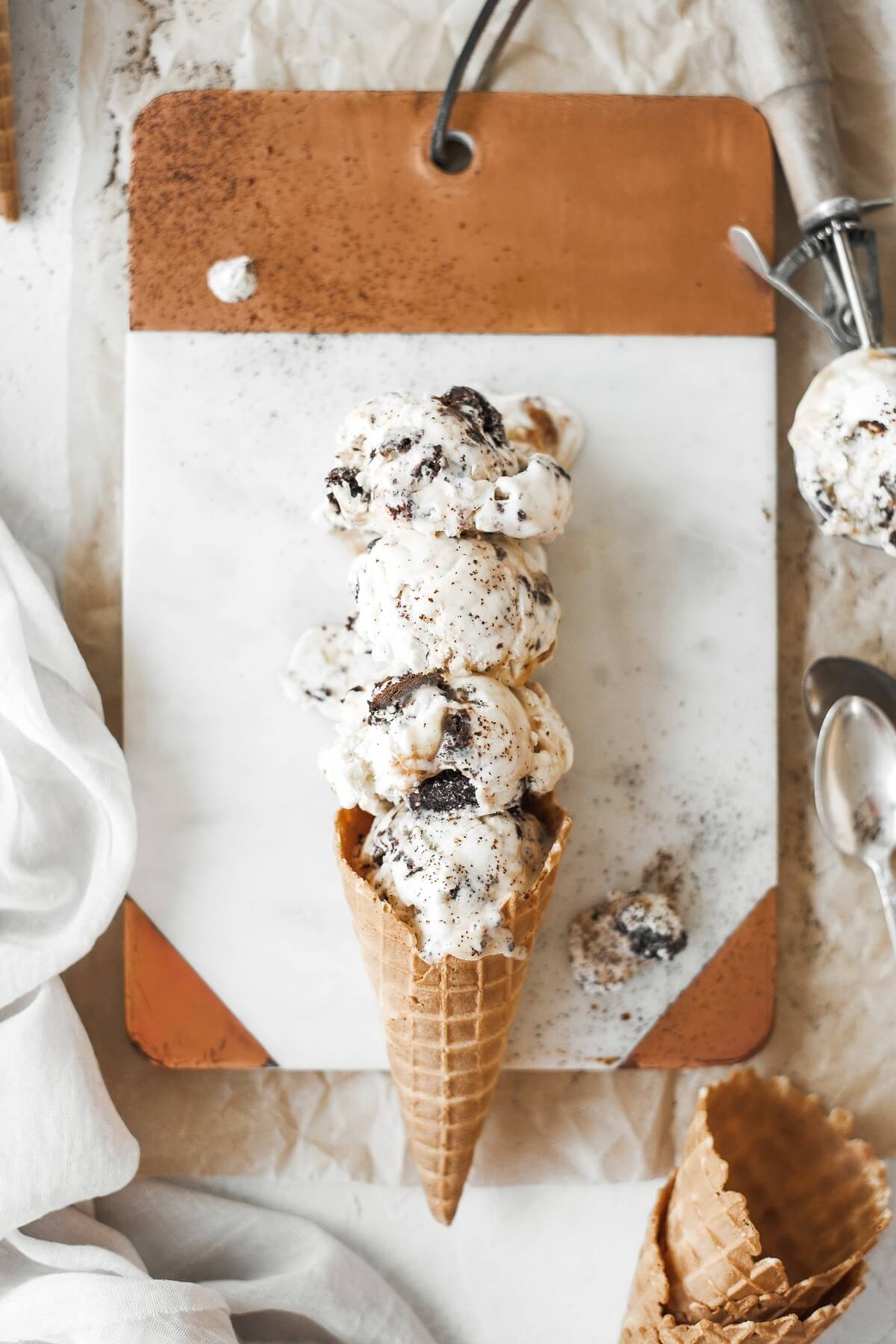 Four scoops of caramel brownie sundae ice cream in a waffle cone.