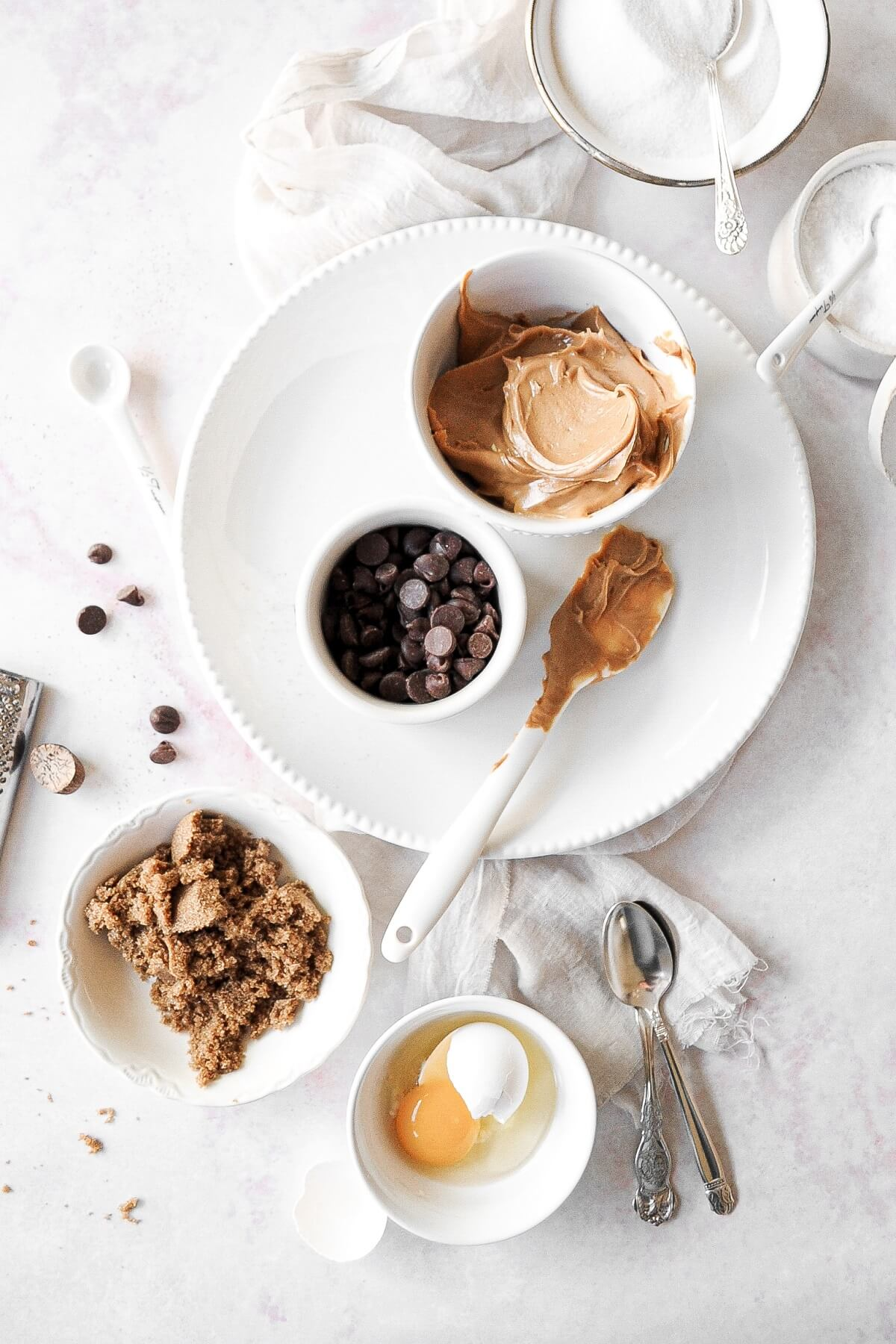 Ingredients for flourless peanut butter chocolate chip cookies arranged in prep bowls.