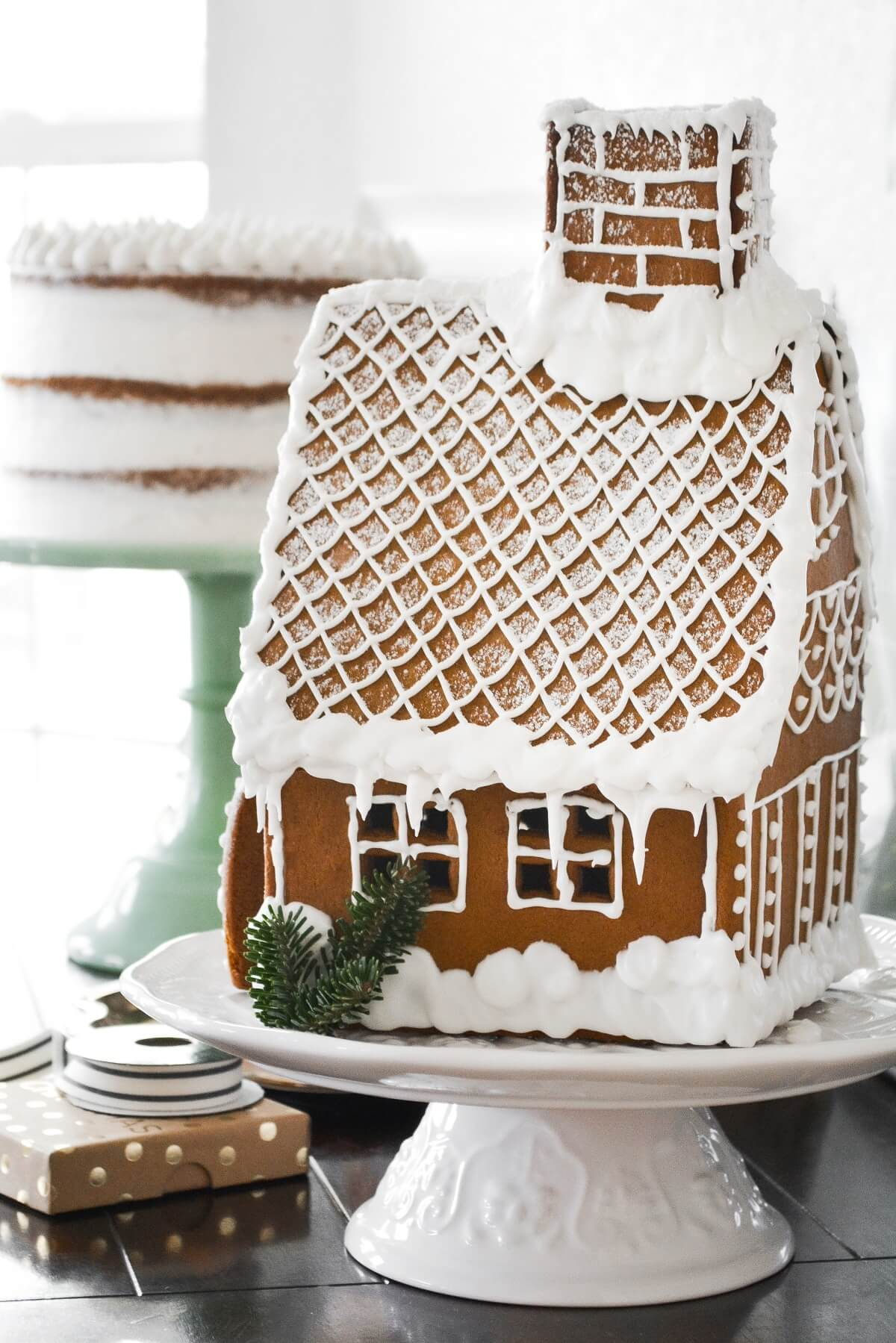 A gingerbread house with a cake in the background.