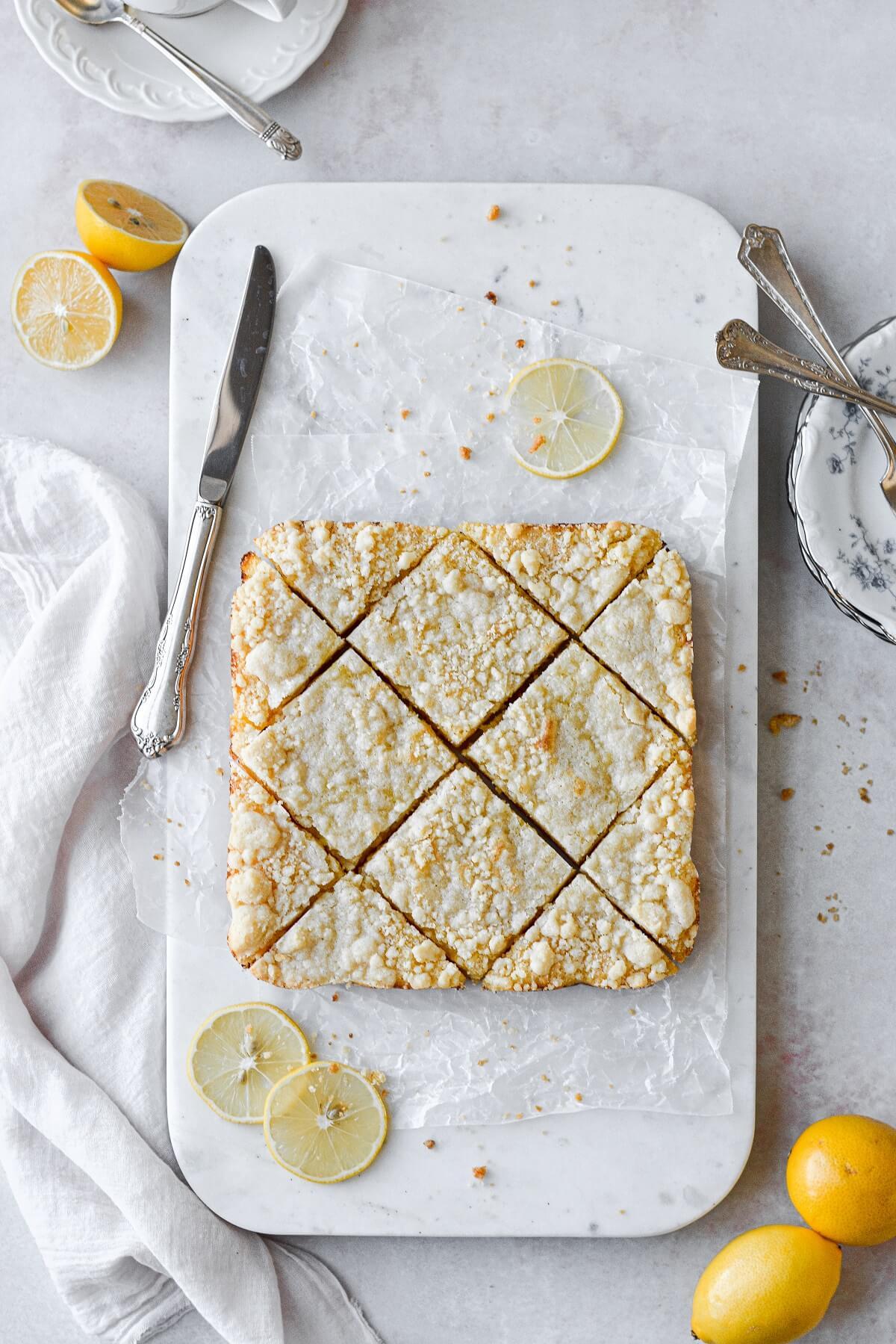 Lemon crumb bars, cut diagonally, on a marble cutting board.