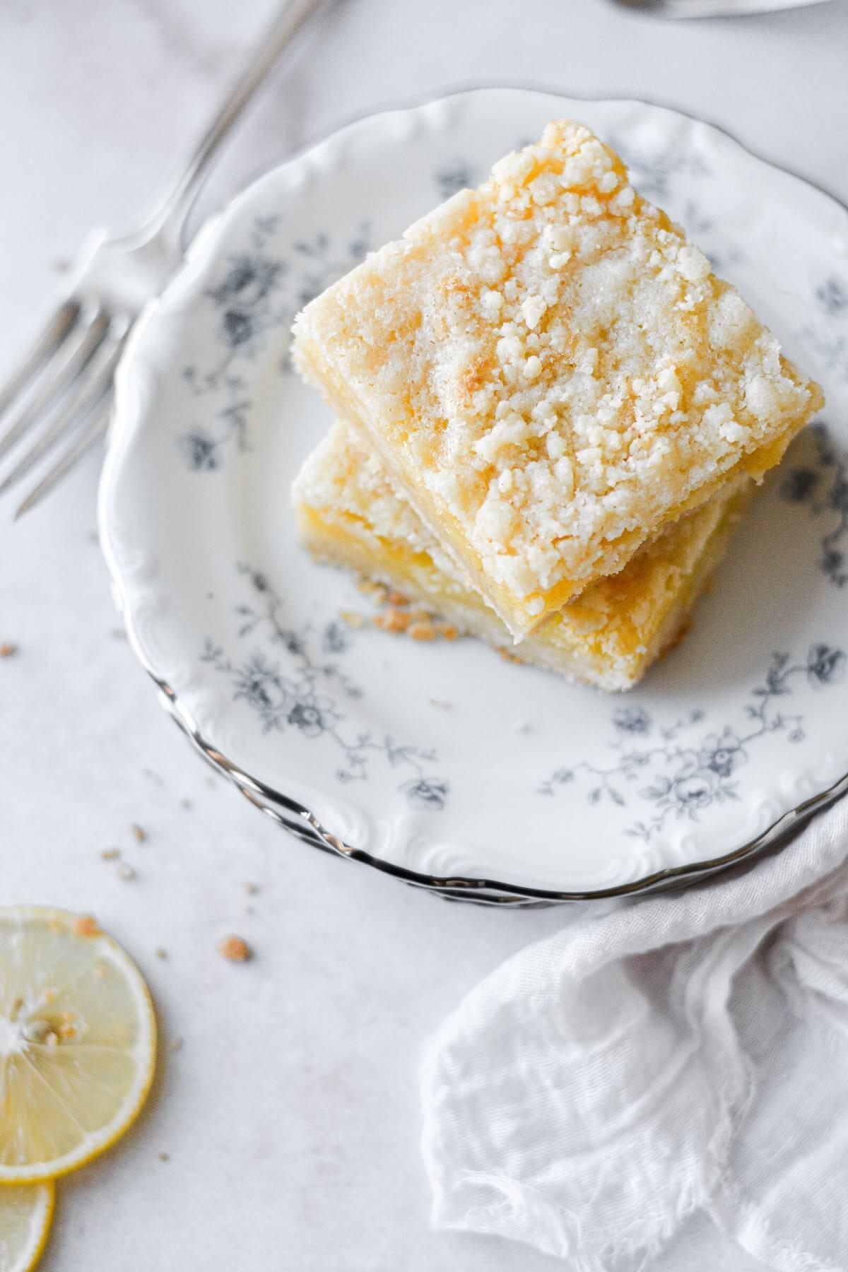 Lemon crumb bars, stacked on flowered plates.