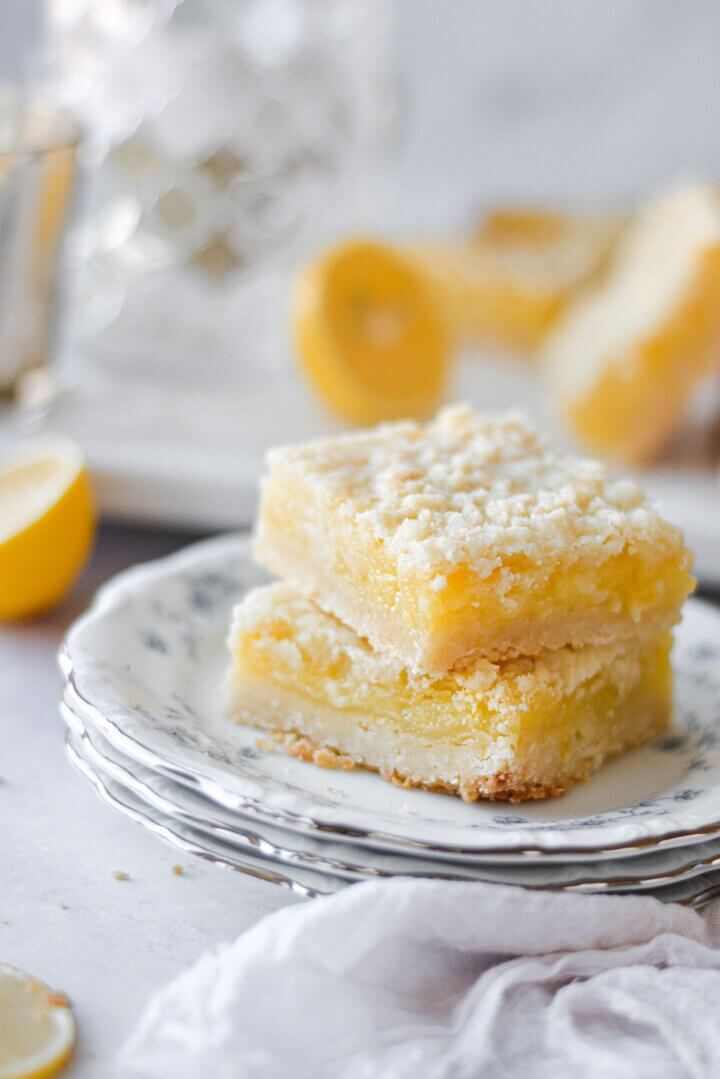 Lemon crumb bars, stacked on flowered plates.
