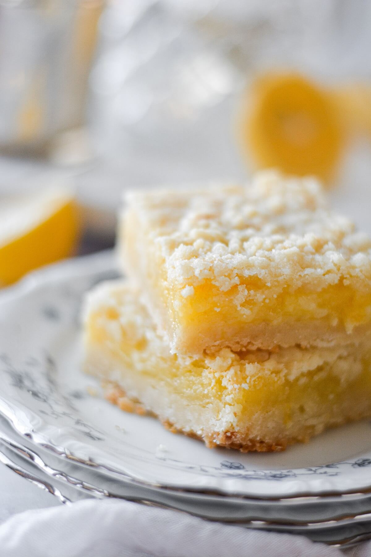 Lemon crumb bars, on a stack of plates.