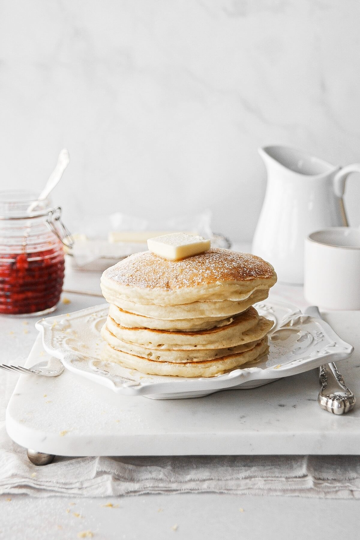 A stack of lemon ricotta pancakes topped with butter.