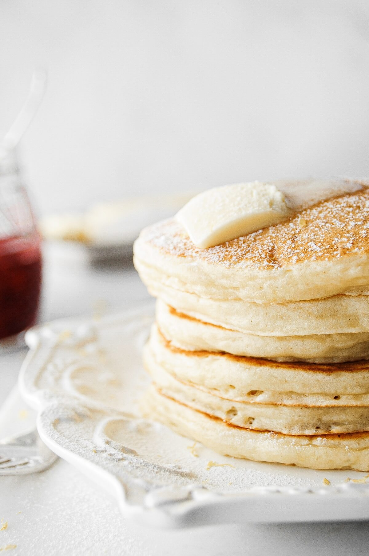 A stack of lemon ricotta pancakes with butter.