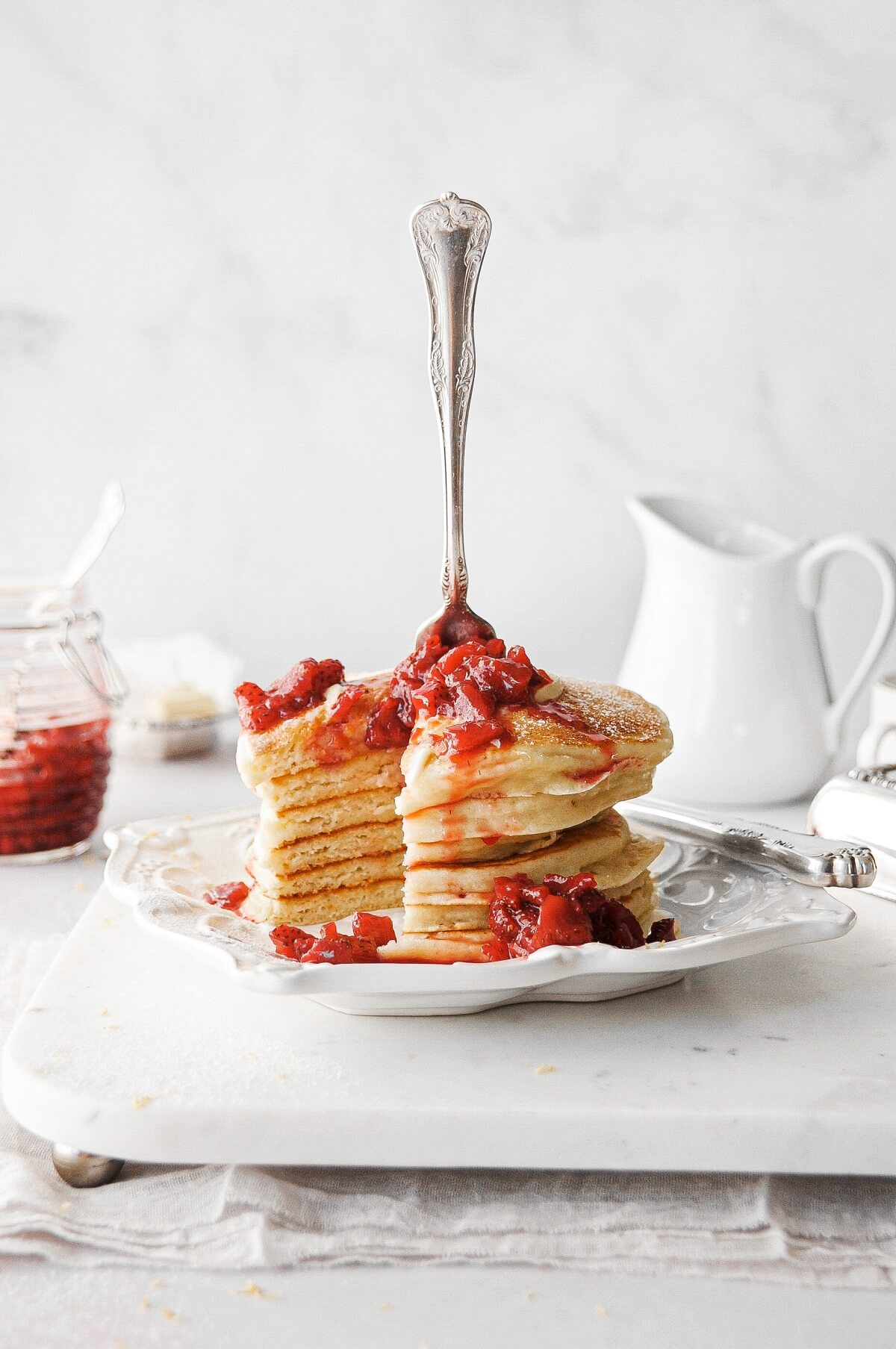 Lemon ricotta pancakes topped with strawberry sauce.
