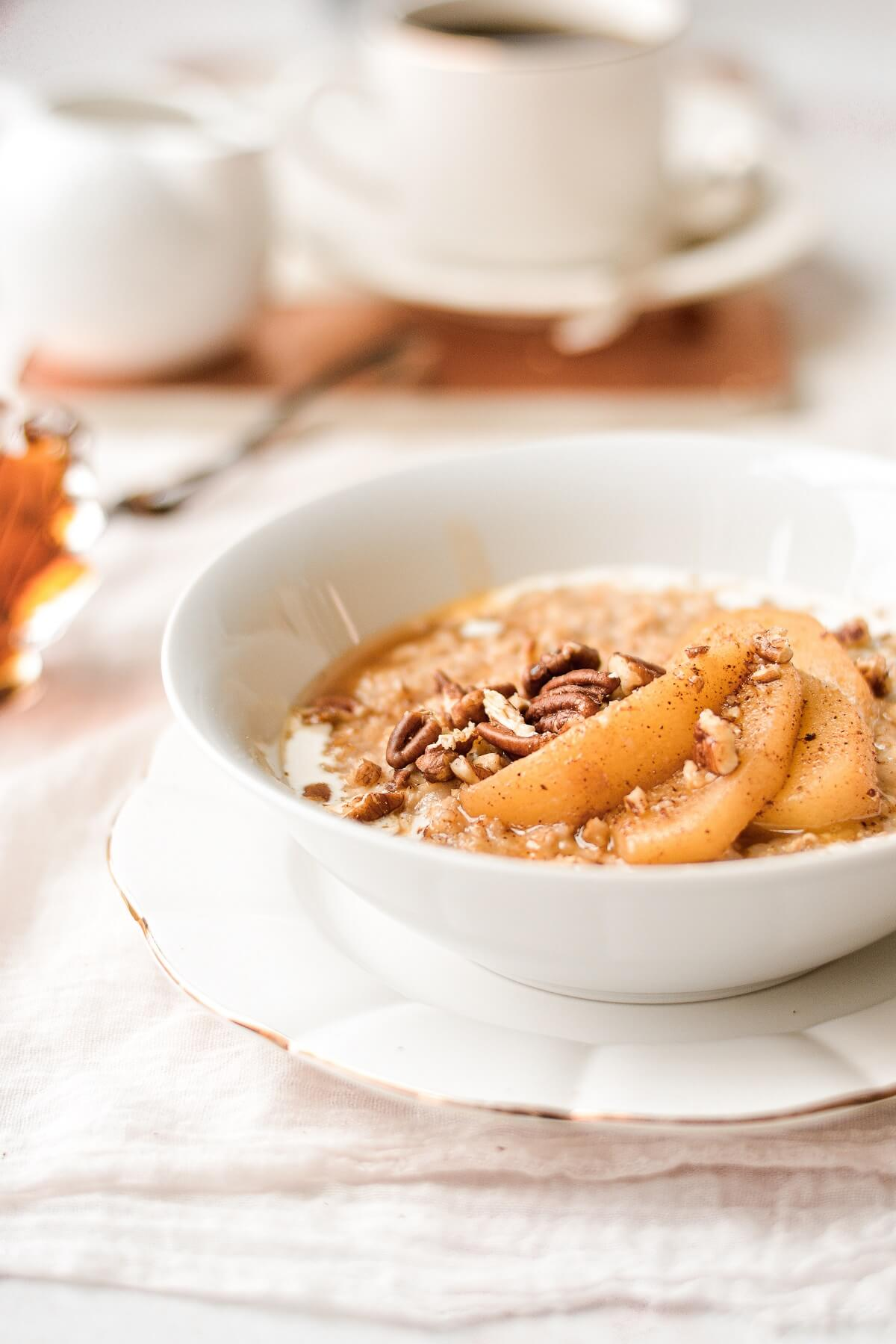A bowl of maple cinnamon oatmeal, topped with sliced apples and pecans.