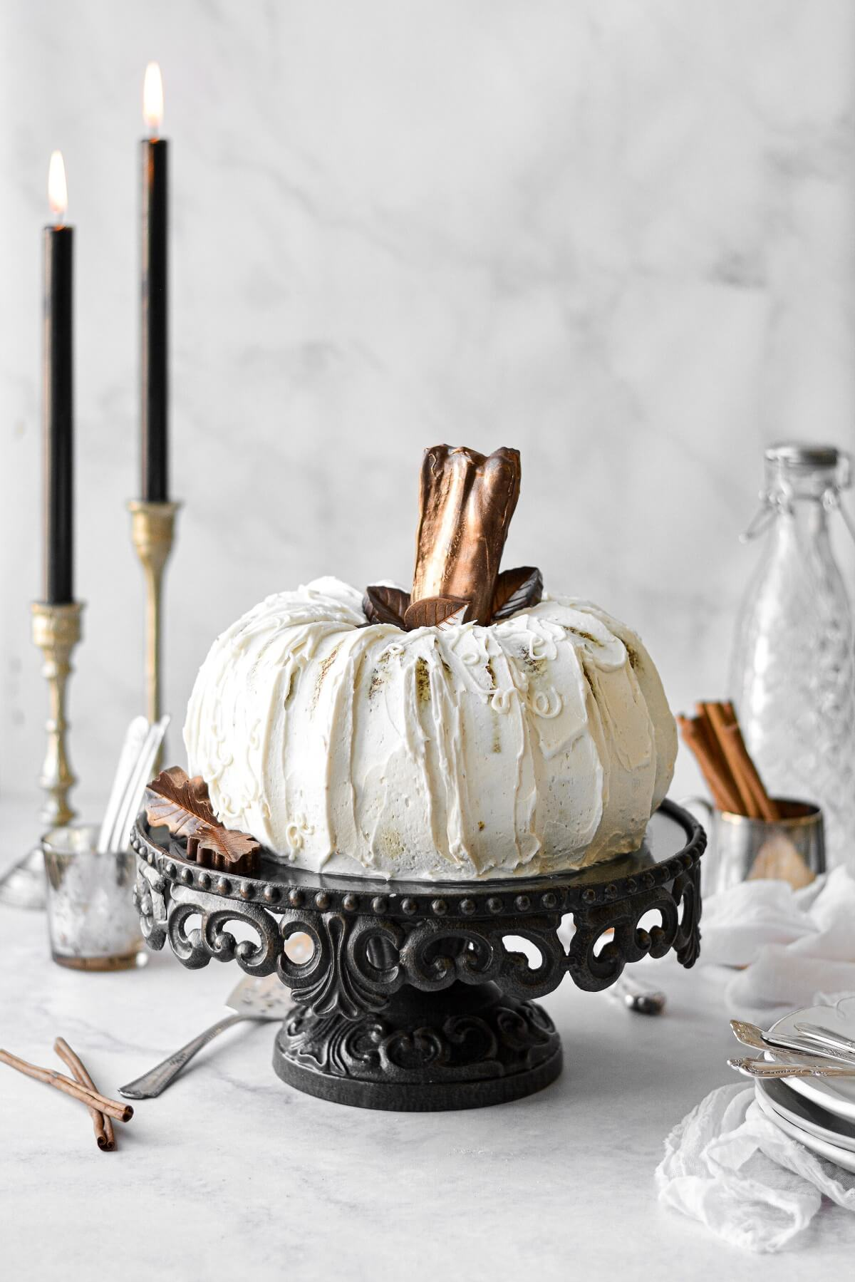 A white pumpkin cake with chocolate leaves and chocolate covered pretzel stem.
